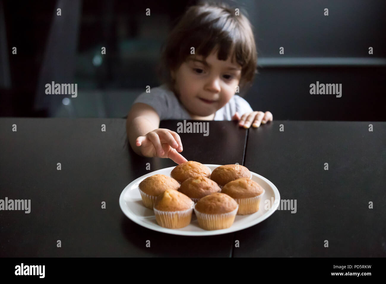 Cute curious little girl reaching muffins on the table - Stock Image