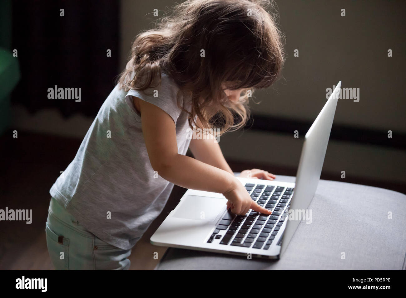 Curious girl using laptop, pc control security for kid concept - Stock Image