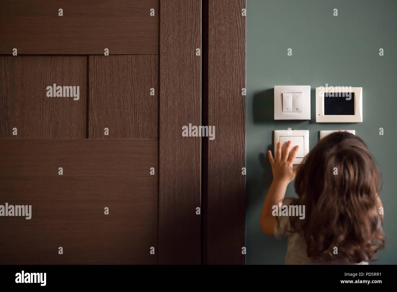 Rear view at little child girl playing turning light switches - Stock Image