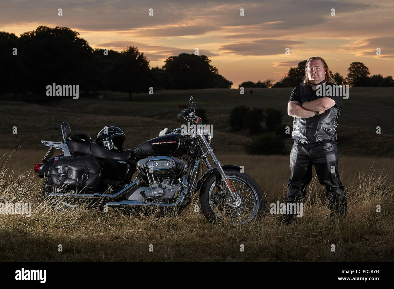 Leather clad biker posing for a photoshoot on his custom Harley Davidson XL883 Sportster Low cruiser motorcycle, on the Beverley westwood, East riding - Stock Image