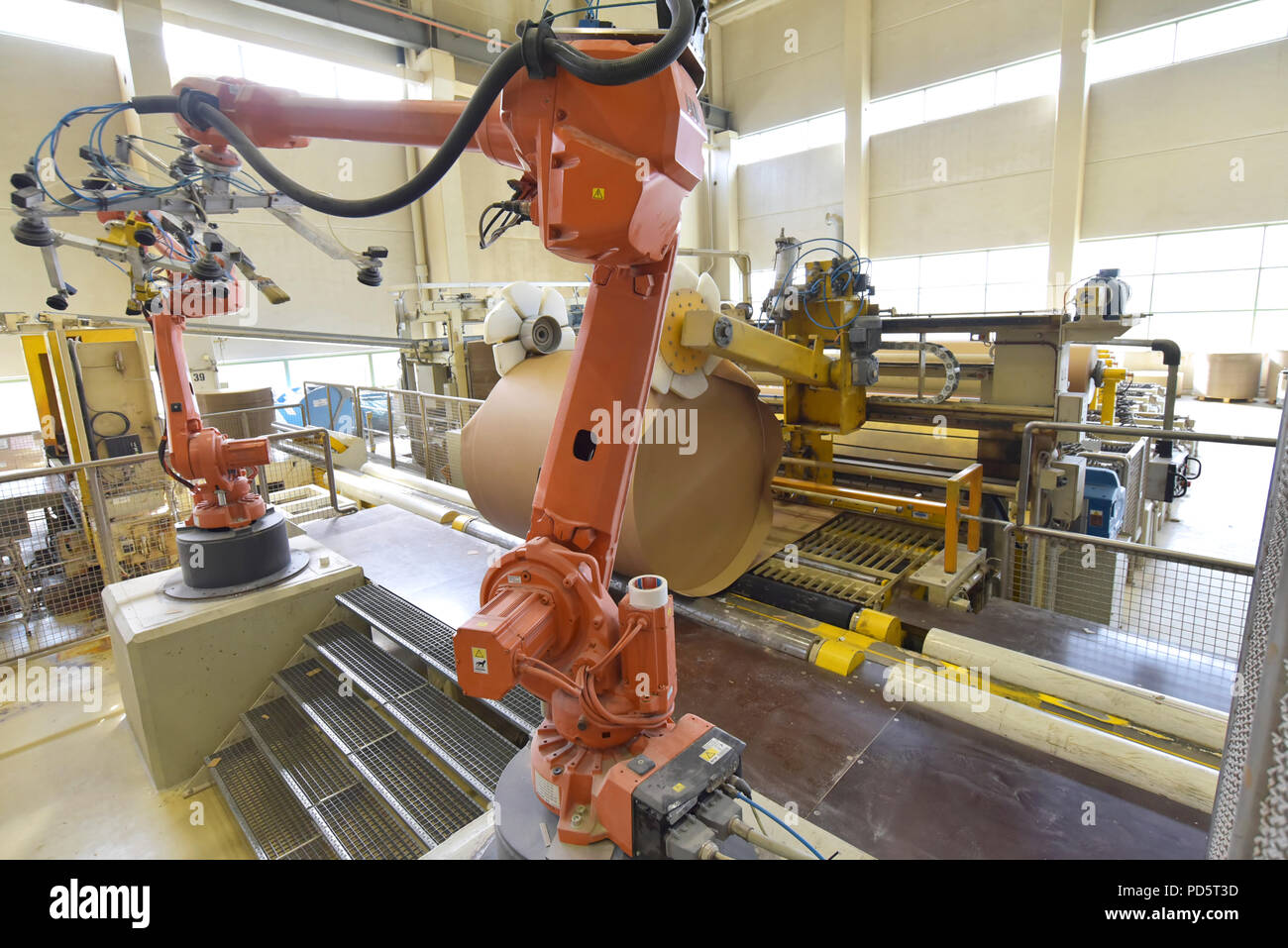 Industrial robot in a paper mill - automation in a modern plant - recycling of waste paper - Stock Image