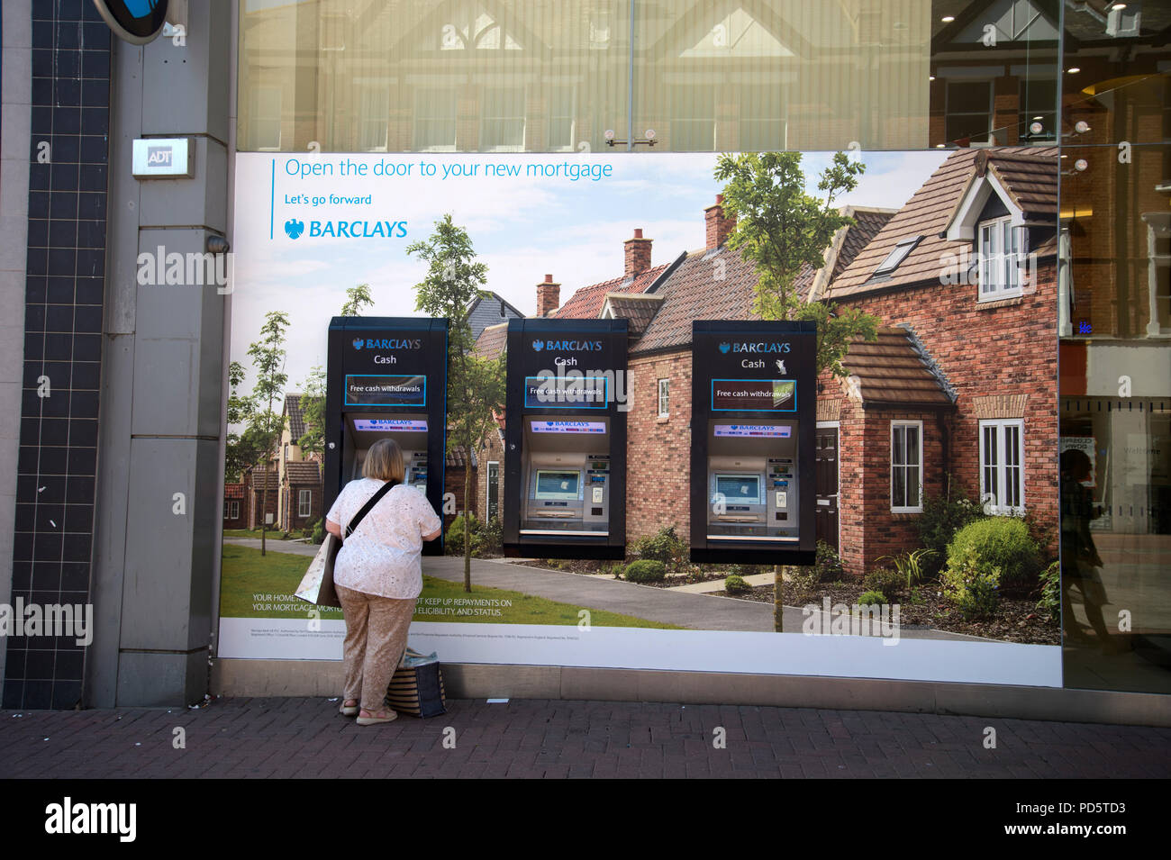 Southend on Sea, Essex. A woman at a Barclays Bank cash machine , set into a giant poster of houses advertisng mortgages - Stock Image