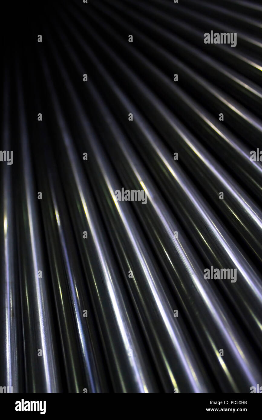 Pattern of lots of shiny stainless industrial metal steel pipe tubes to cut weld process and work with - Stock Image