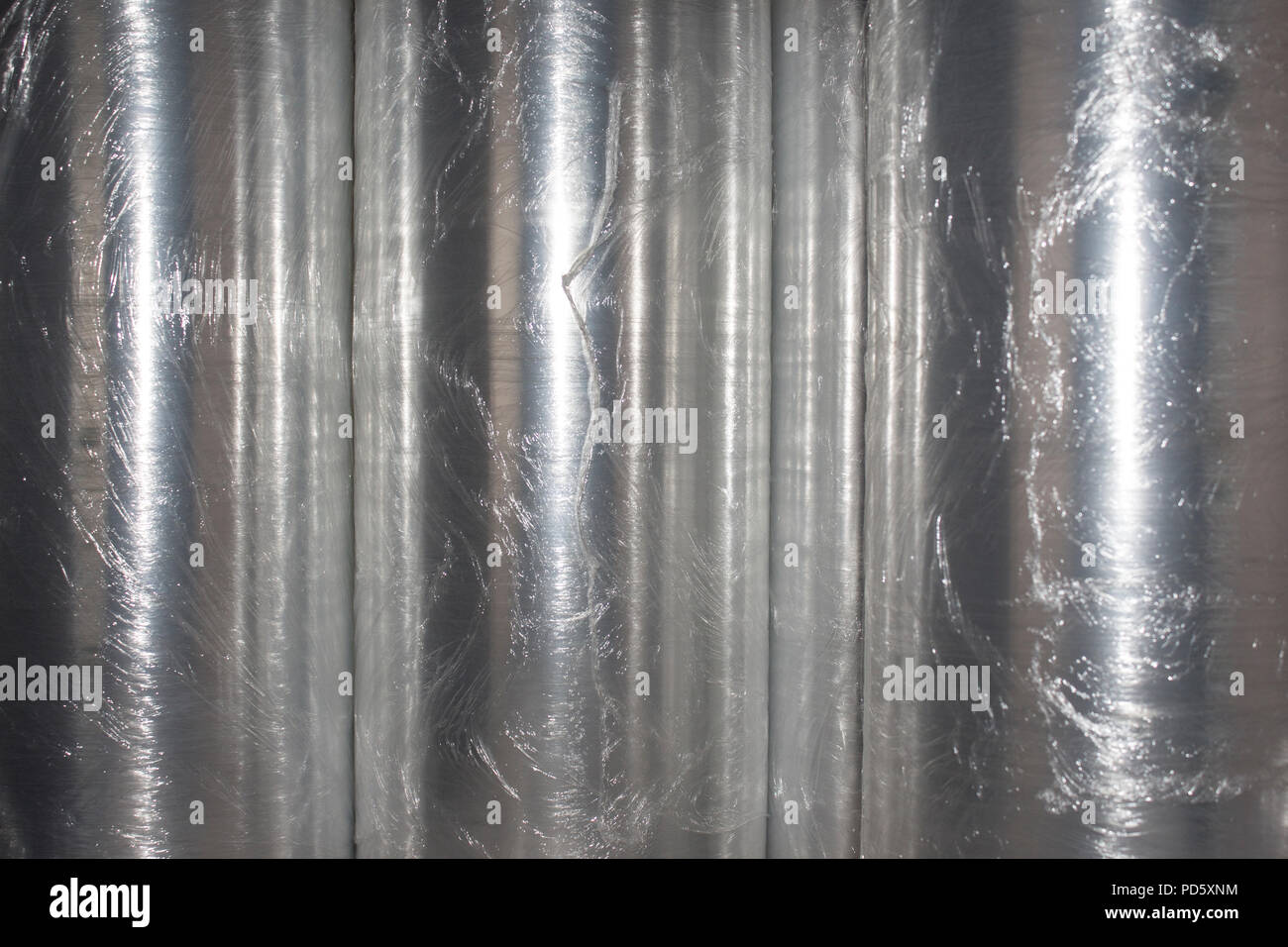 Rolls of clear plastic wrapping foil for product packaging and safe industrial shipping transport - Stock Image