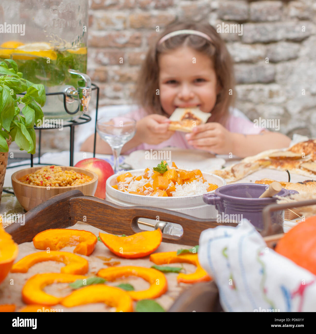 Little girl is eating pie. Family dinner in the courtyard outdoors. Autumn vegetables and fruits on the table. Dining table . A special place for text. - Stock Image