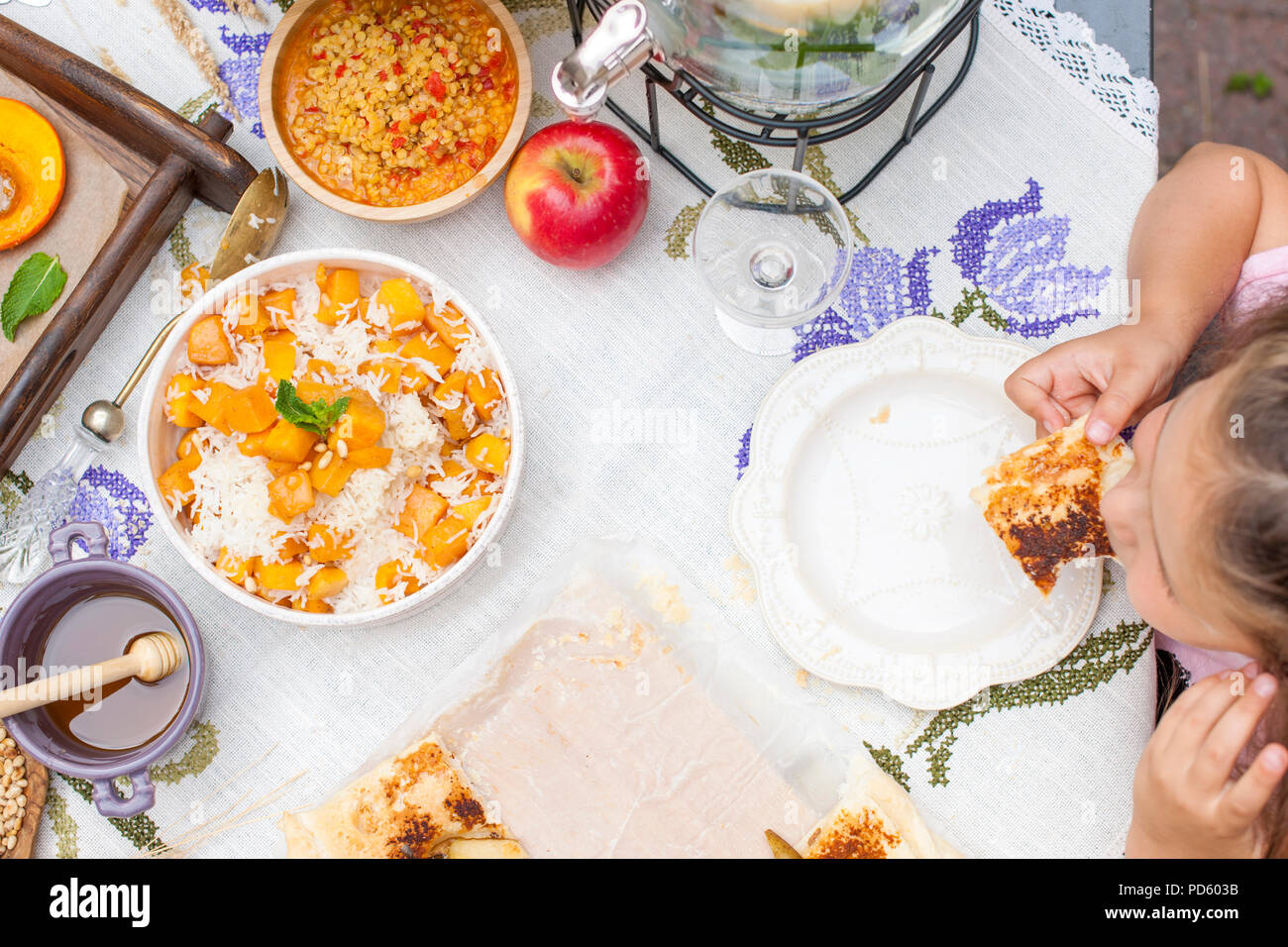 Little girl is eating pie. Family dinner in the courtyard outdoors. Autumn vegetables and fruits on the table. Dining table top view. A special place for text. - Stock Image