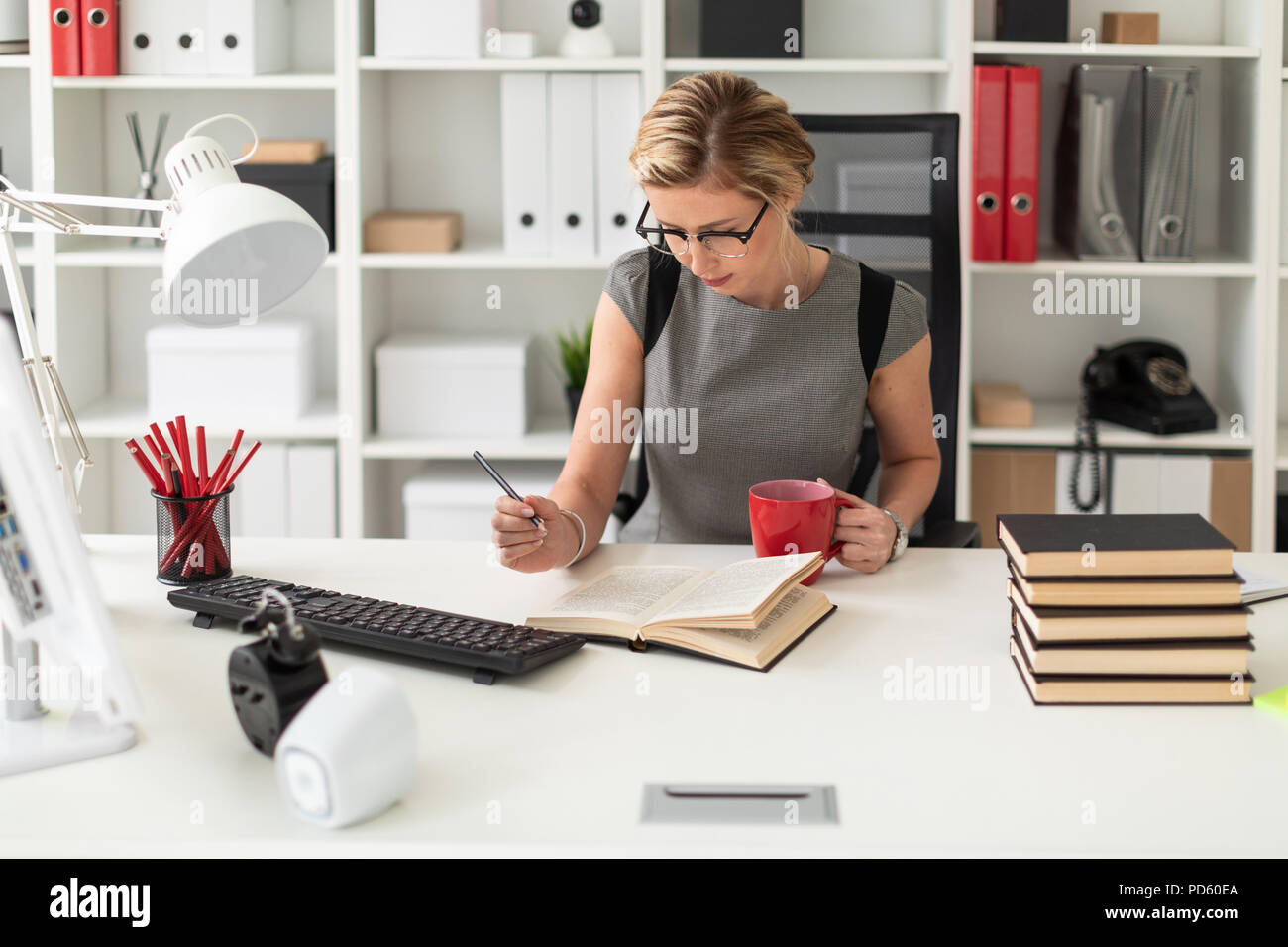A young girl is sitting at a table in the office, holding a pencil and a red cup in her hand. Before the girl lies an open book. Stock Photo