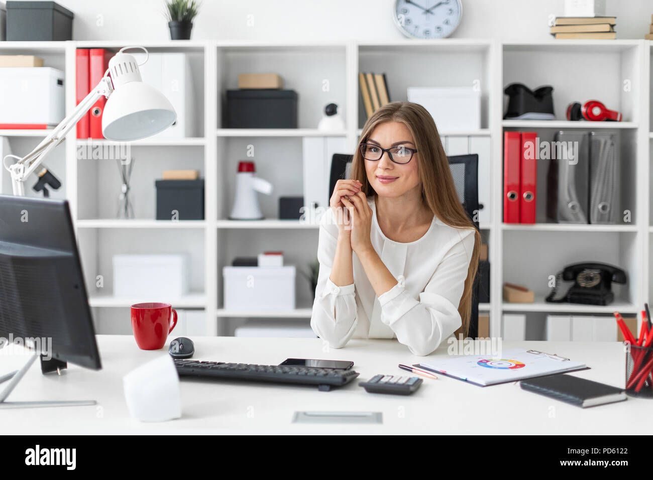 A young girl is sitting at the computer desk in the office. - Stock Image