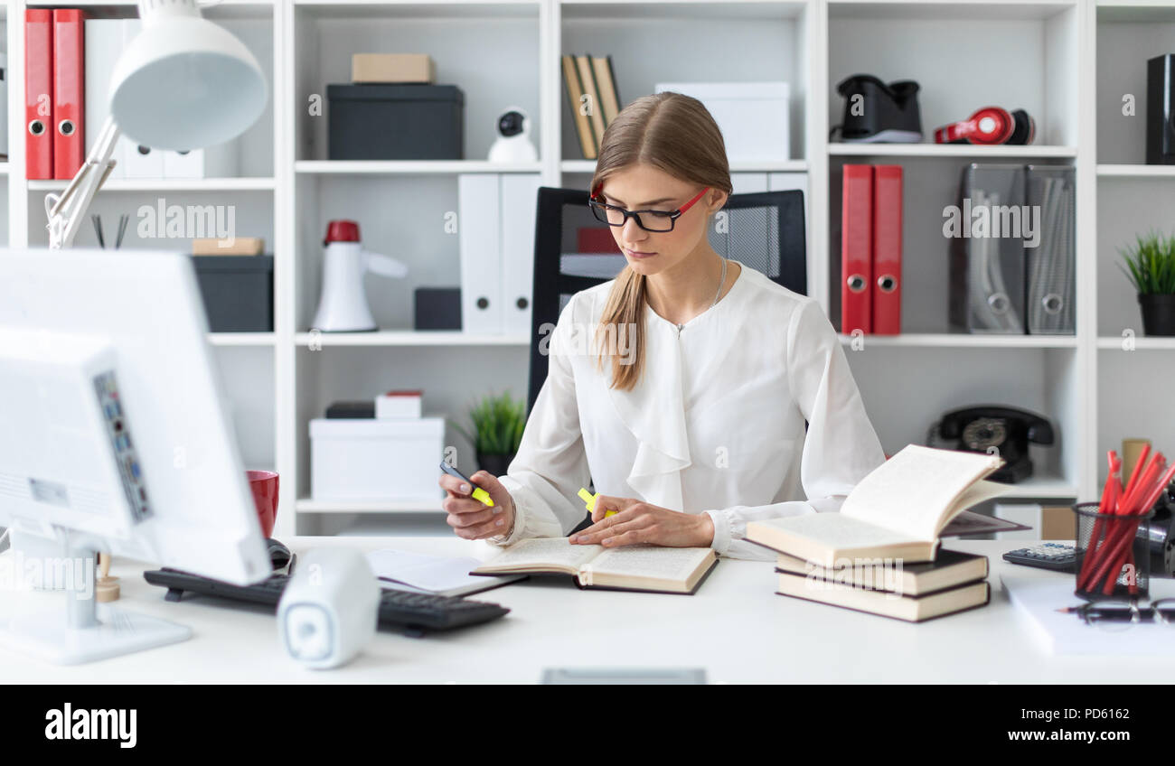 A young girl sits at a table in the office and holds a yellow marker in her hand. Before the girl lies an open book. - Stock Image