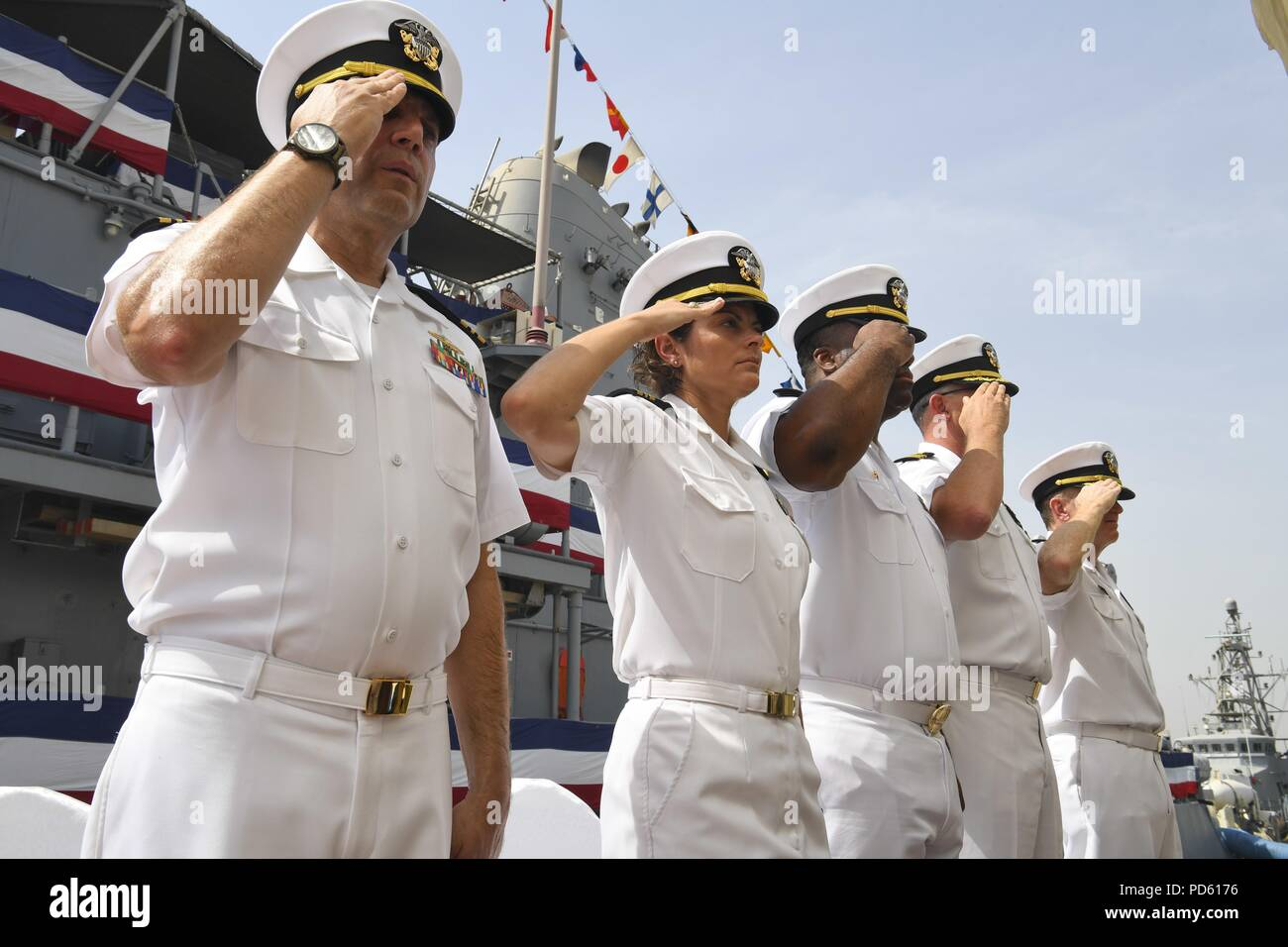 180711-N-TB177-1031 MANAMA, Bahrain (July 11, 2018) Officers salute during a change of command ceremony for the Avenger-class mine countermeasures ship USS Gladiator (MCM 11) on Naval Support Activity Bahrain, July 11, 2018. Gladiator is forward deployed to the U.S. 5th Fleet area of operations in support of naval operations to ensure maritime stability and security in the Central region, connecting the Mediterranean and the Pacific through the western Indian Ocean and three strategic choke points. (U.S. Navy photo by Mass Communication Specialist 2nd Class Kevin J. Steinberg/Released). () Stock Photo