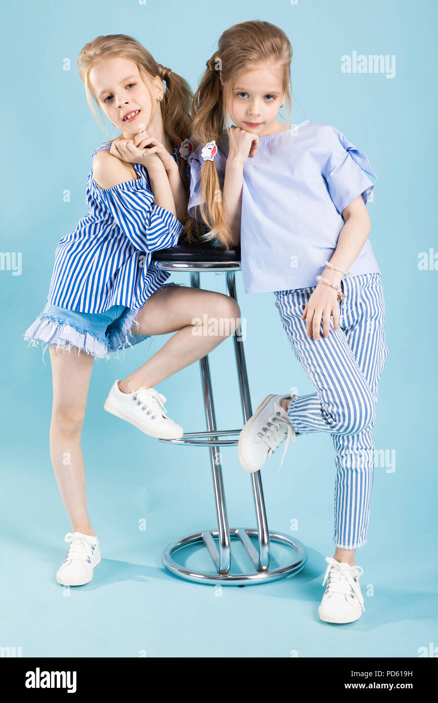 1c811f2f6369b Girls twins in light blue clothes are posing near a bar stool on a blue  background