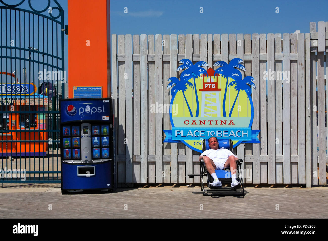 Older white man rests in a folding chair on Coney Island boardwalk during heat wave, Brooklyn on May 8th, 2015, New York City. (Photo by Wojciech Migd - Stock Image