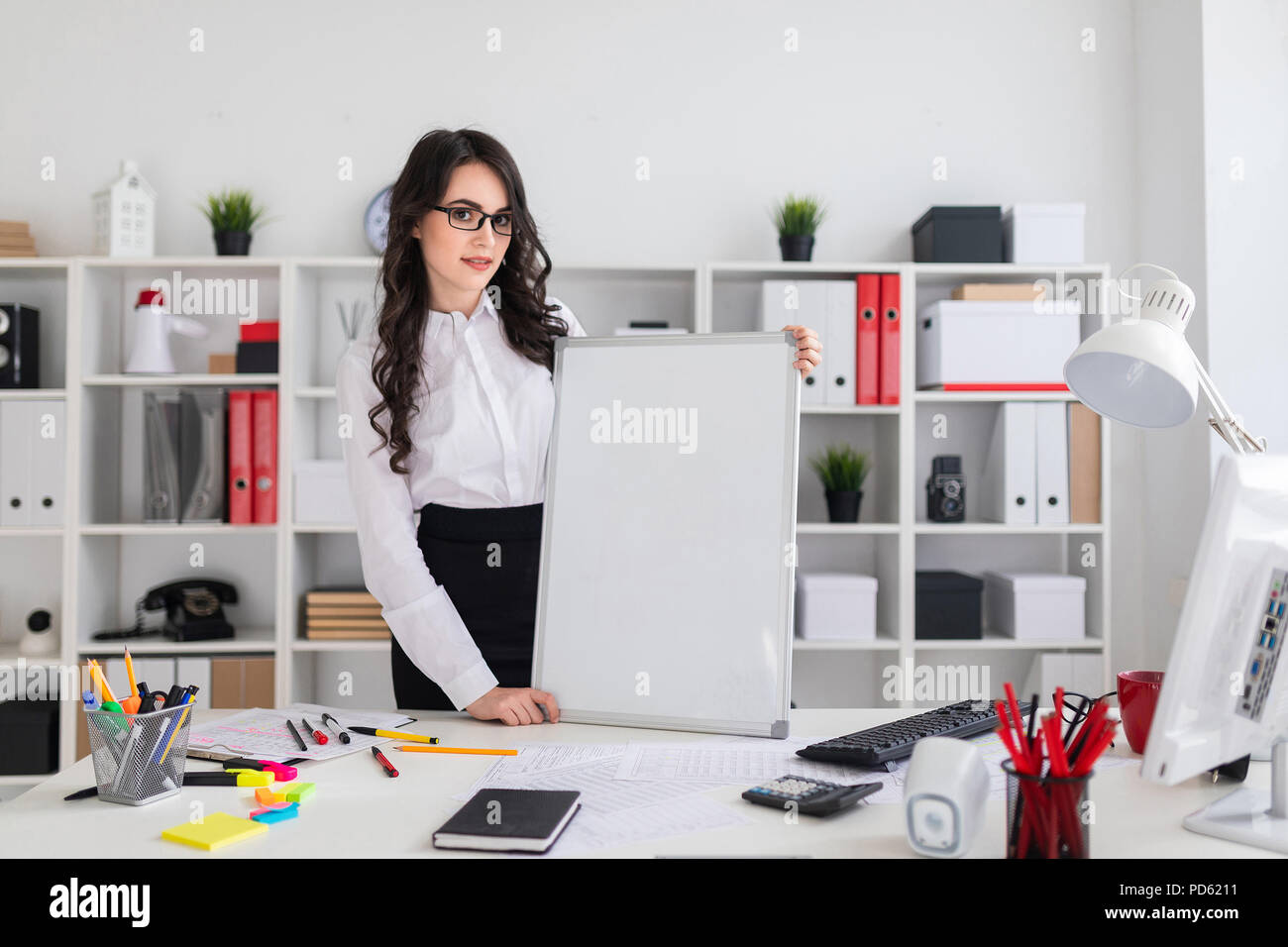 Beautiful young girl stands near an office desk with an empty magnetic board - Stock Image