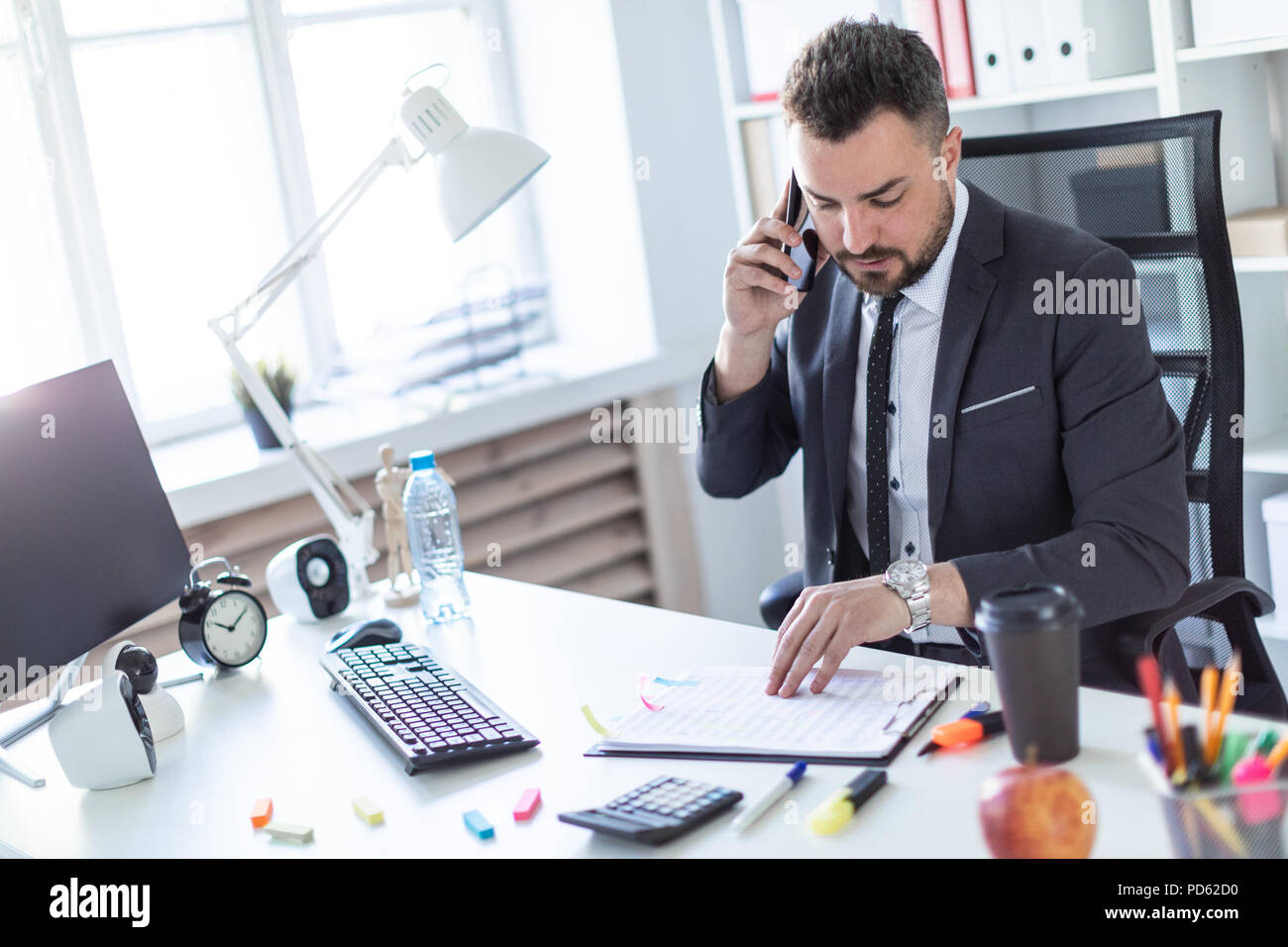 A man is sitting in the office at the table, talking on the phone and flipping through documents. - Stock Image