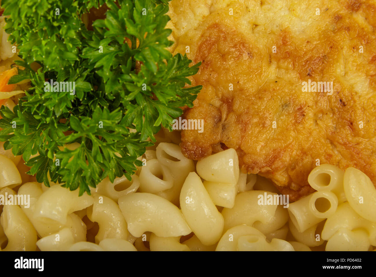 Pasta with a piece of grilled meat and salad. - Stock Image