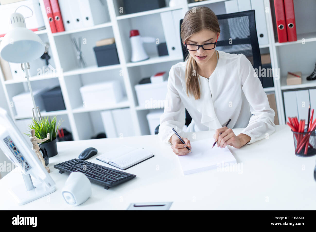 A young girl sits at a table in the office and holds pencils in her hands. Before the girl lies an open book. - Stock Image