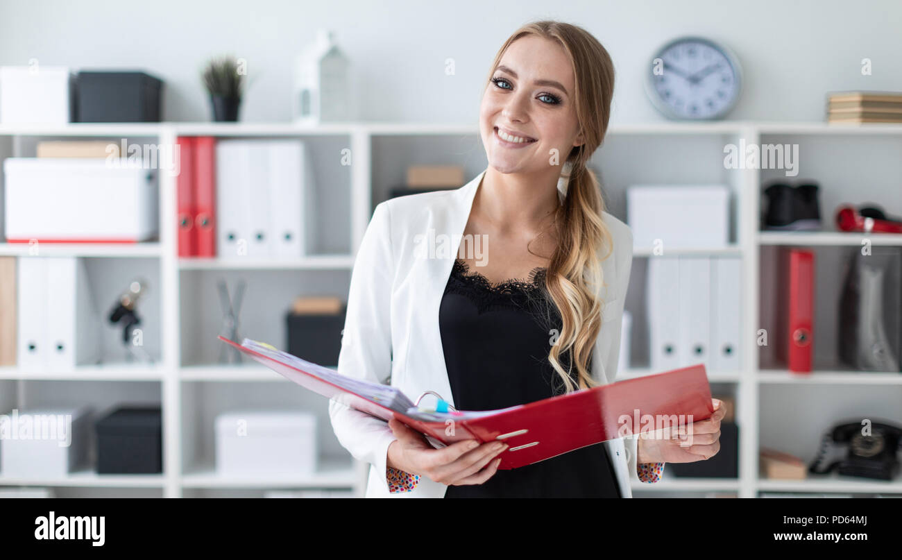 A young girl stands in the office next to the shelf and holds a folder with documents in her hands. - Stock Image