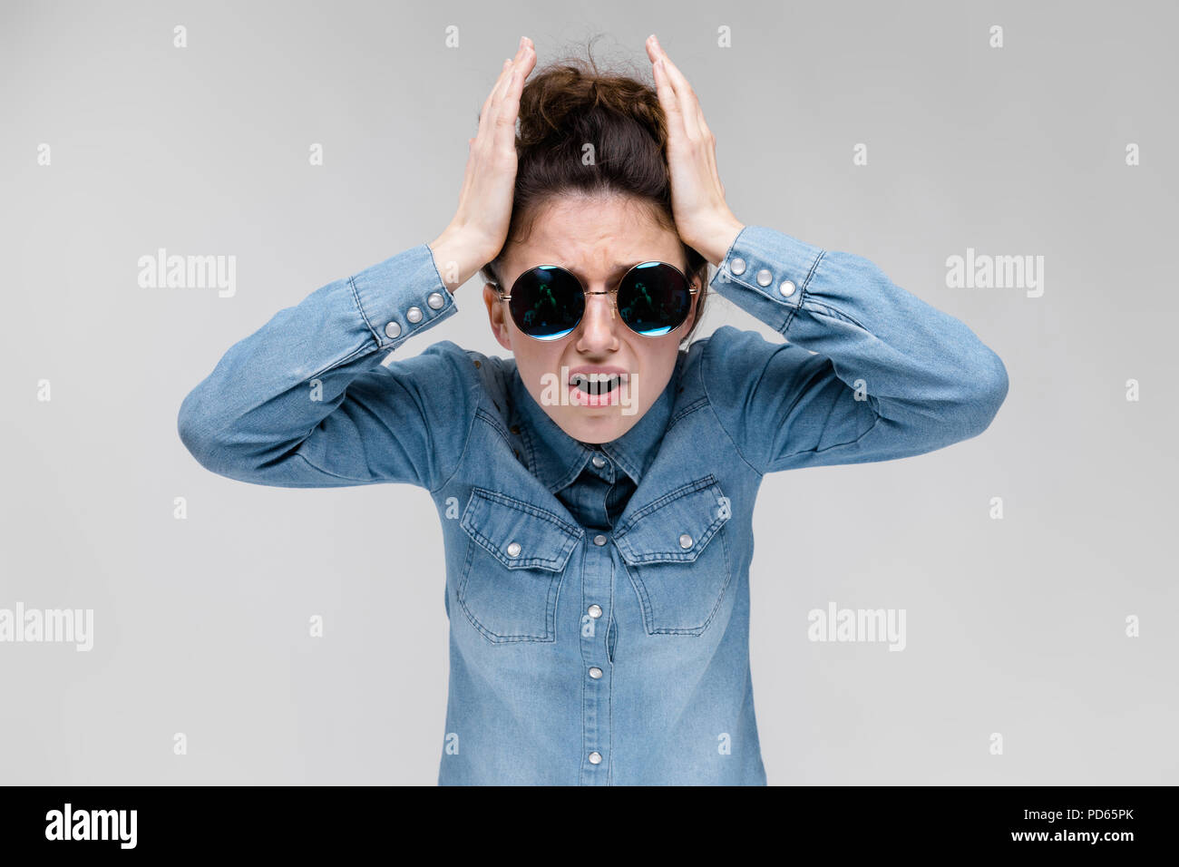 Young brunette girl in round glasses. Hairs are gathered in a bun. The girl holds her hands behind her head. - Stock Image