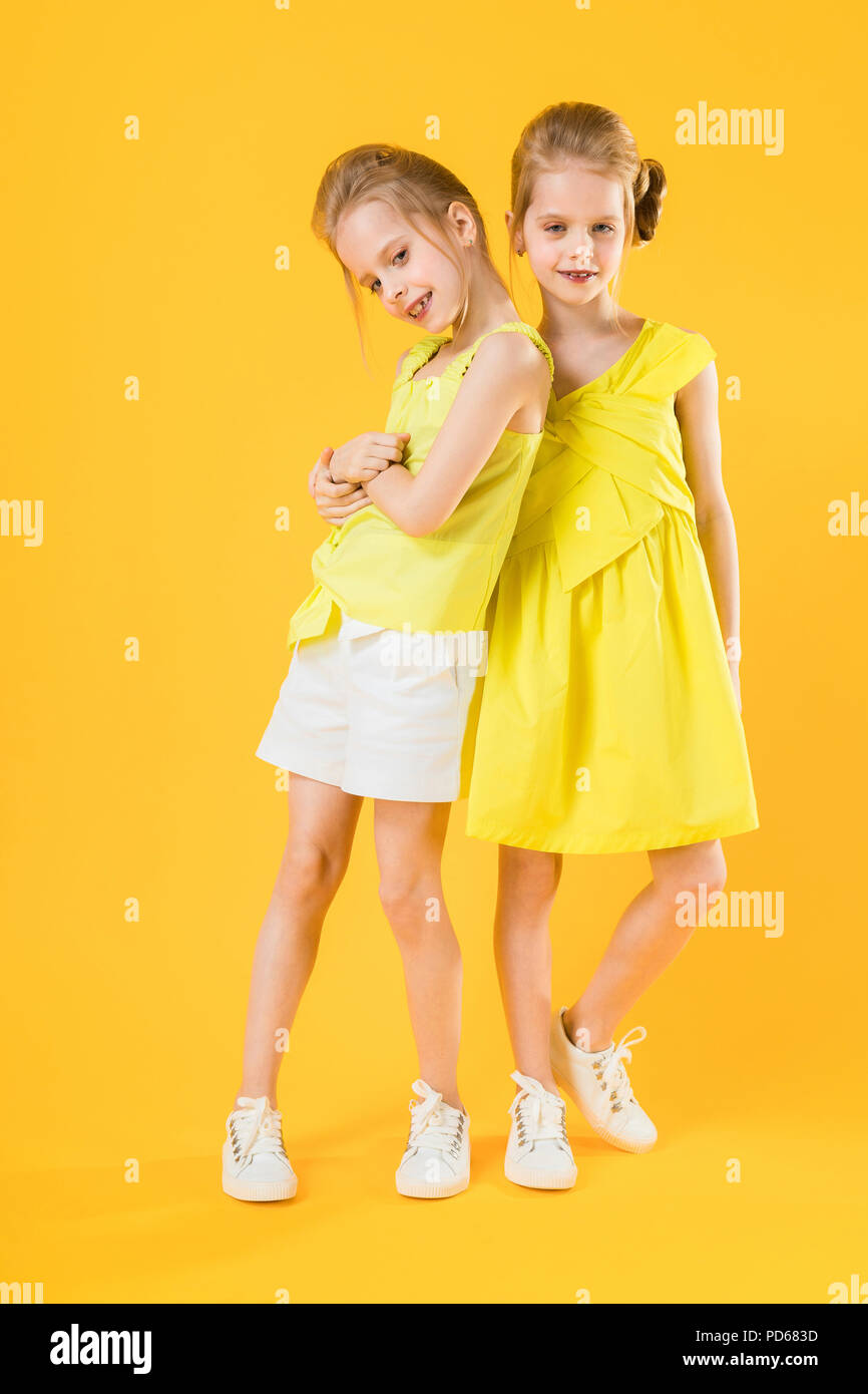 The girls of the twins stand together on a yellow background. Stock Photo
