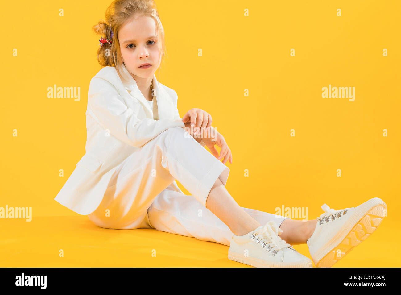 A teenage girl in white clothes sits stretching her legs forward on a yellow background. Stock Photo