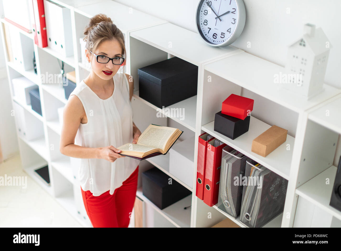 A young girl stands near the shelf and holds an open book in her hands. - Stock Image