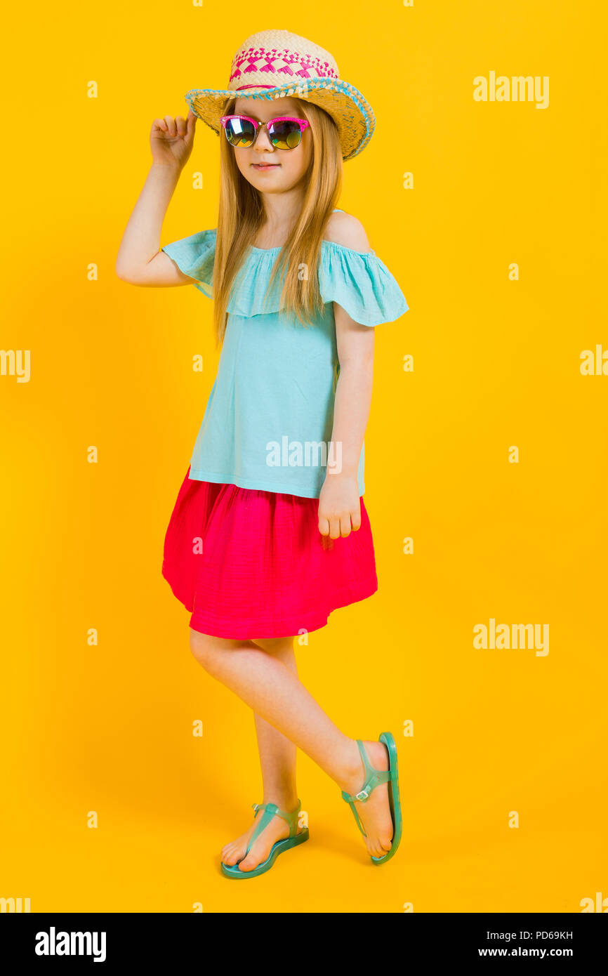 Girl with red hair on a yellow background. A charming girl in bright summer  clothes 8f248ed94da