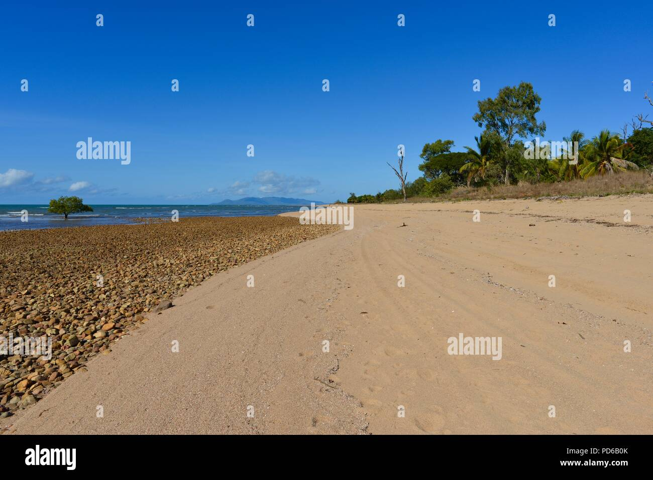 Rocky beach merging with a sandy beach, natural patterns, Coastal scenes from tropical north Queensland, Toolakea QLD, Australia - Stock Image
