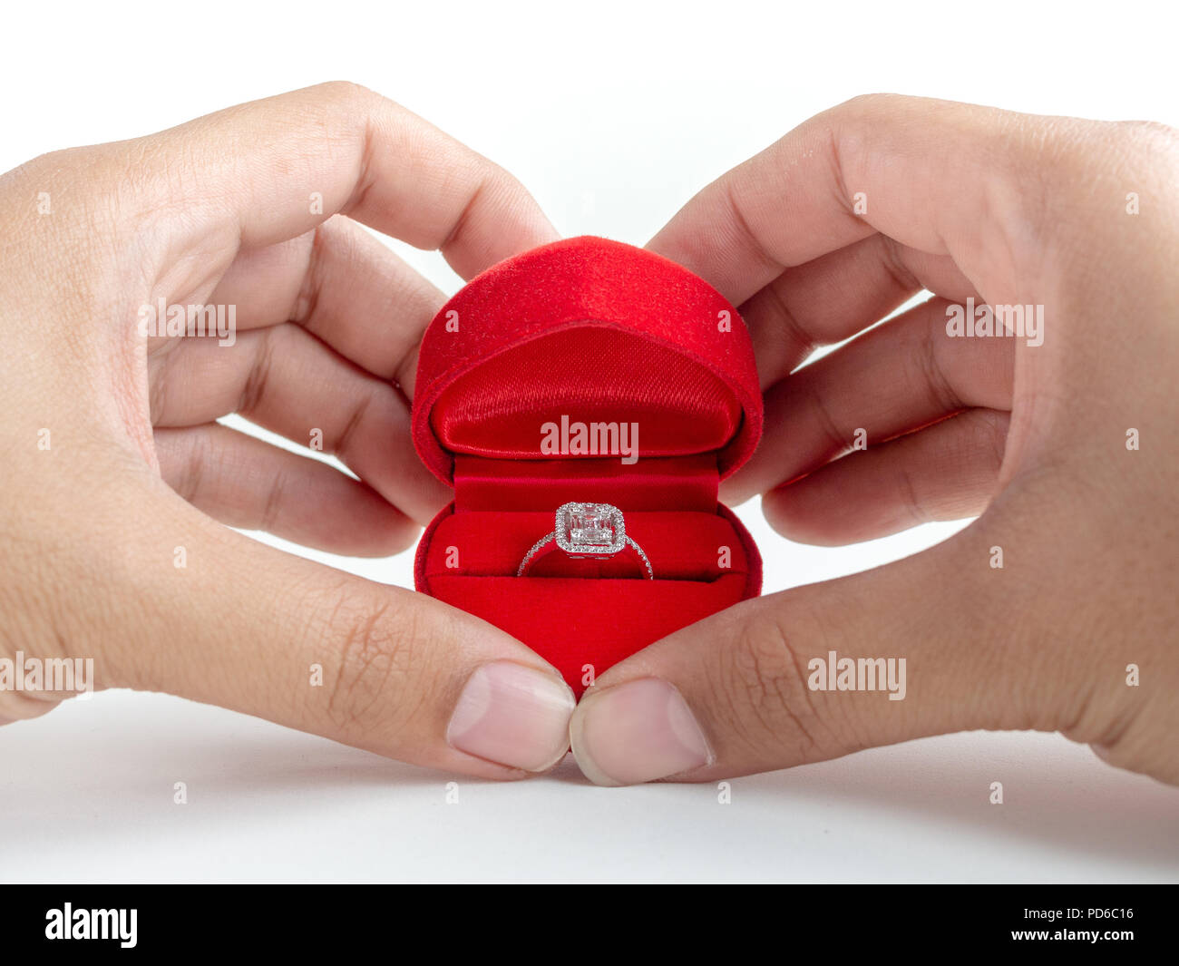 3a2cb9cab Diamond ring in red heart shape box in hands isolated on white background.