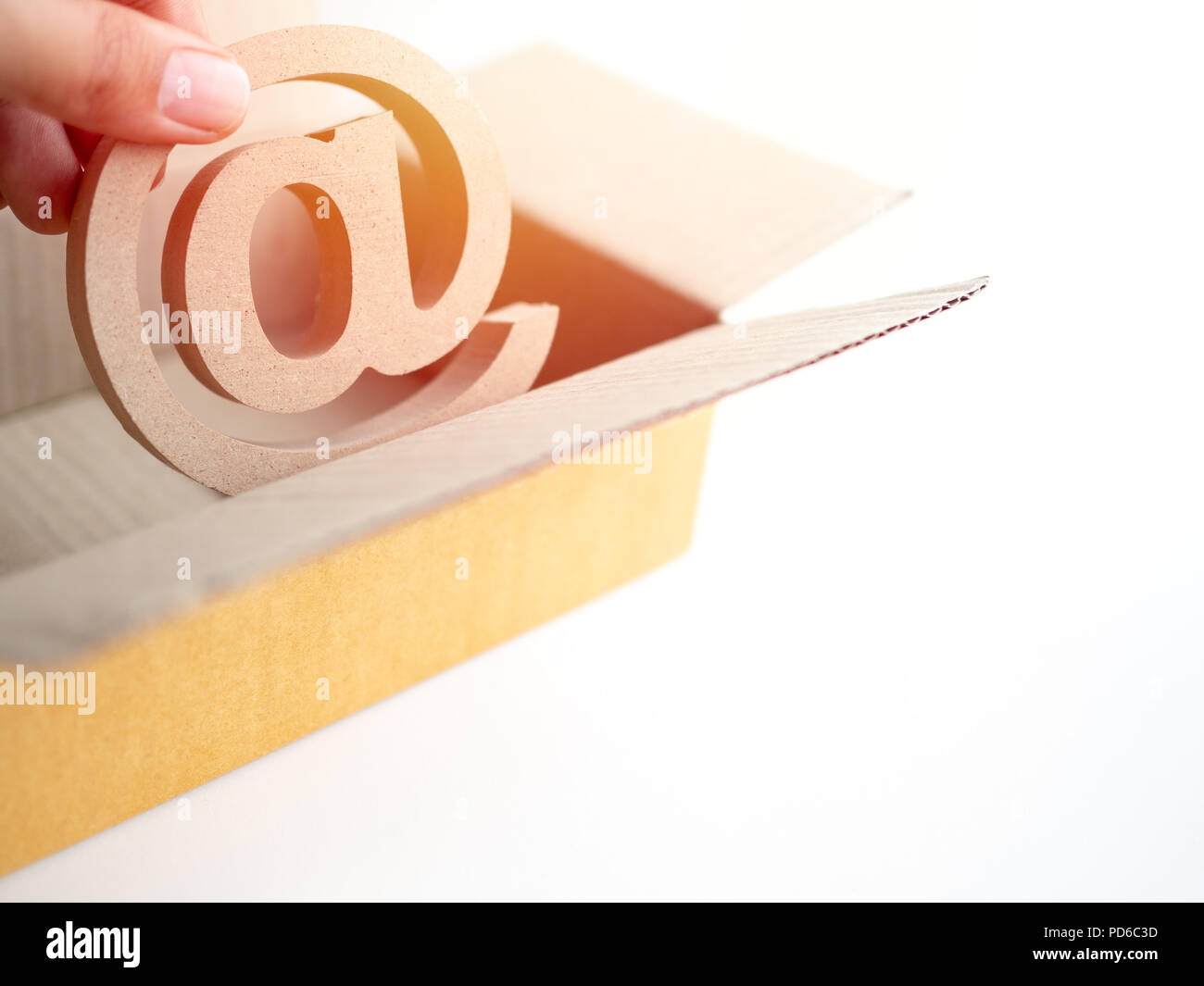 Hand picking wooden E-mail address symbol from the brown paper box, arroba icon in the cardboard carton box isolated on white background with copy spa - Stock Image