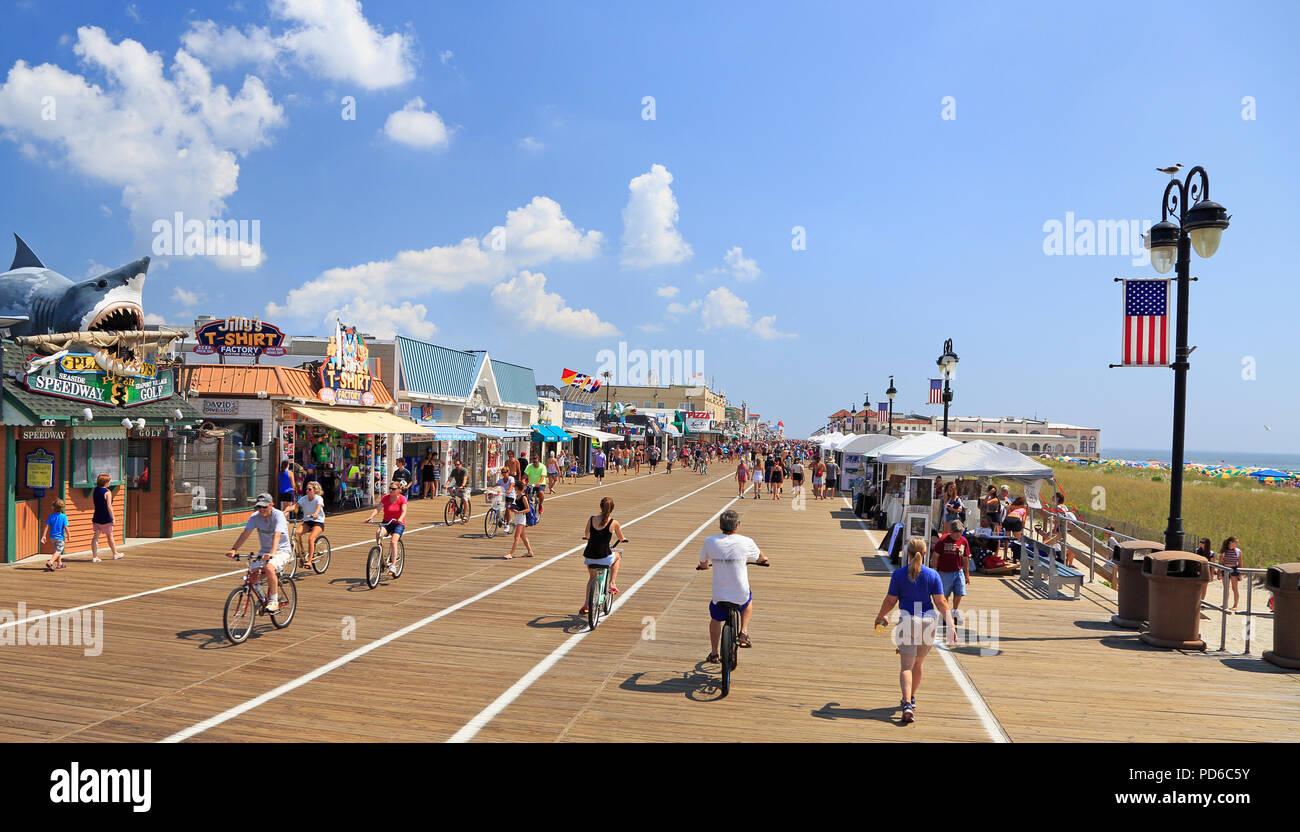 People walking and biking along the boardwalk in Ocean City, New Jersey, USA - Stock Image