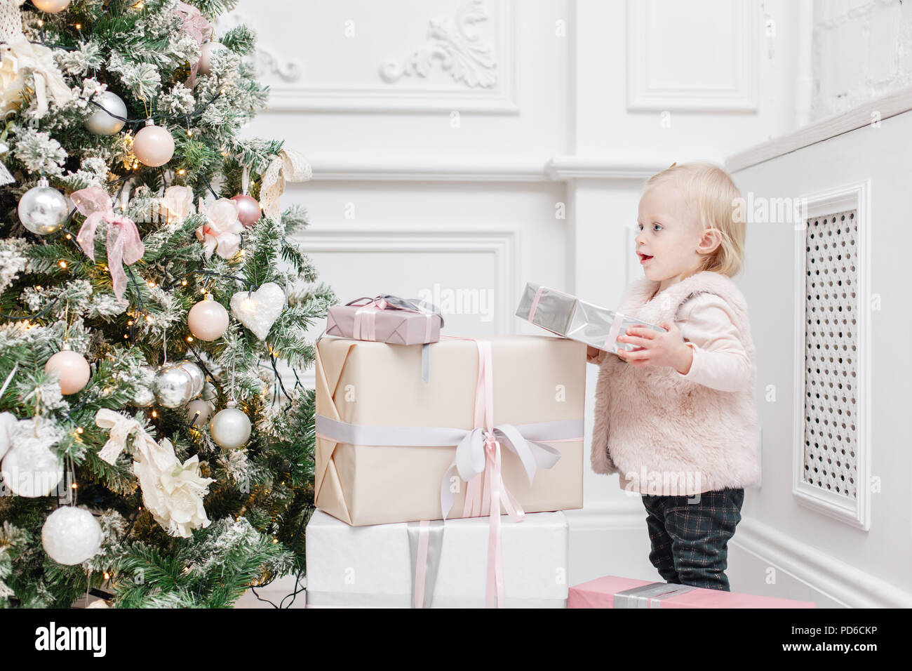 Cute baby and christmas gifts. Little child having fun near ...