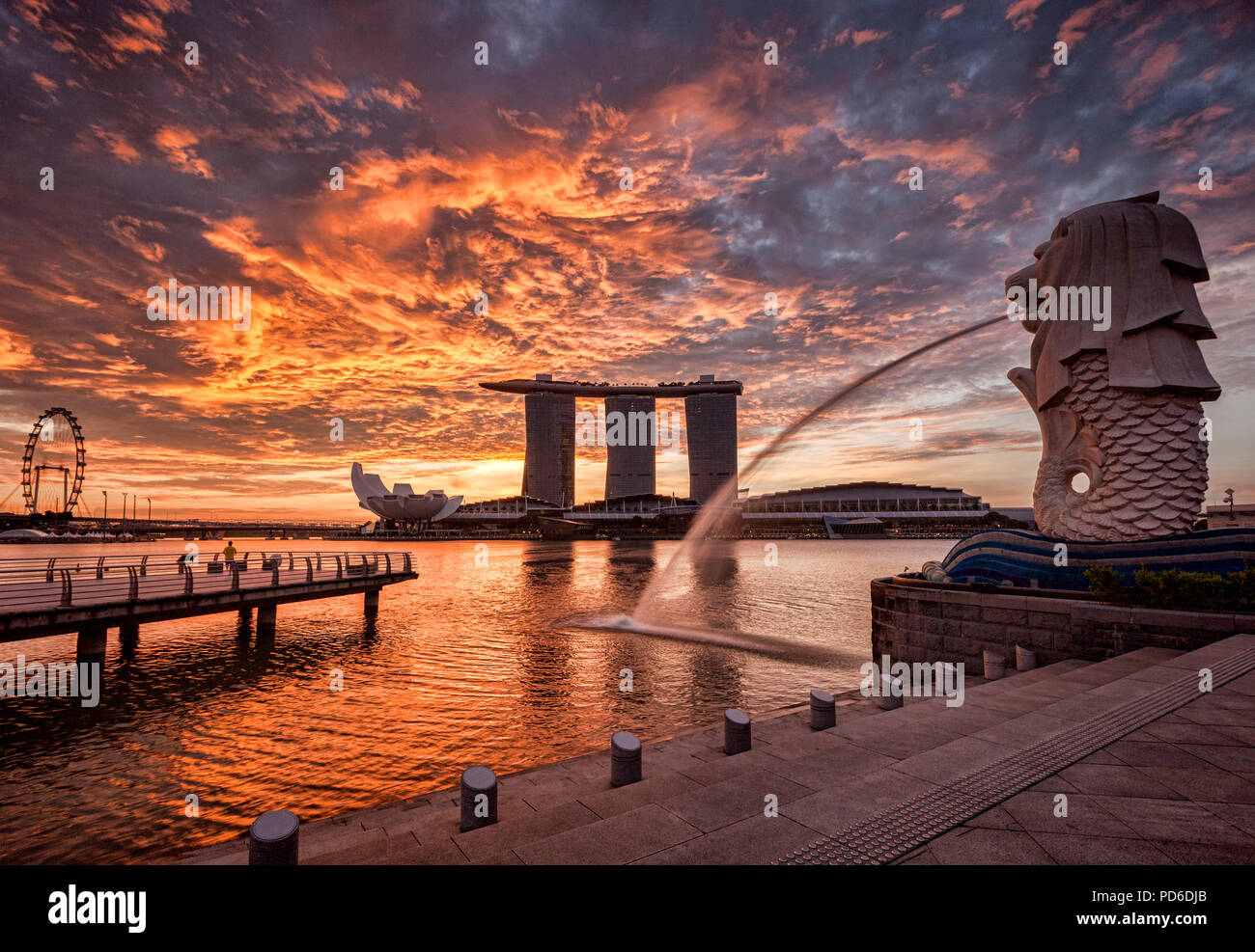 Singapore skyline at sunrise, with the Merlion, the Marina Bay Sands, the Art ans Science Museum and the Singapore Flyer, all under a dramatic sunrise - Stock Image