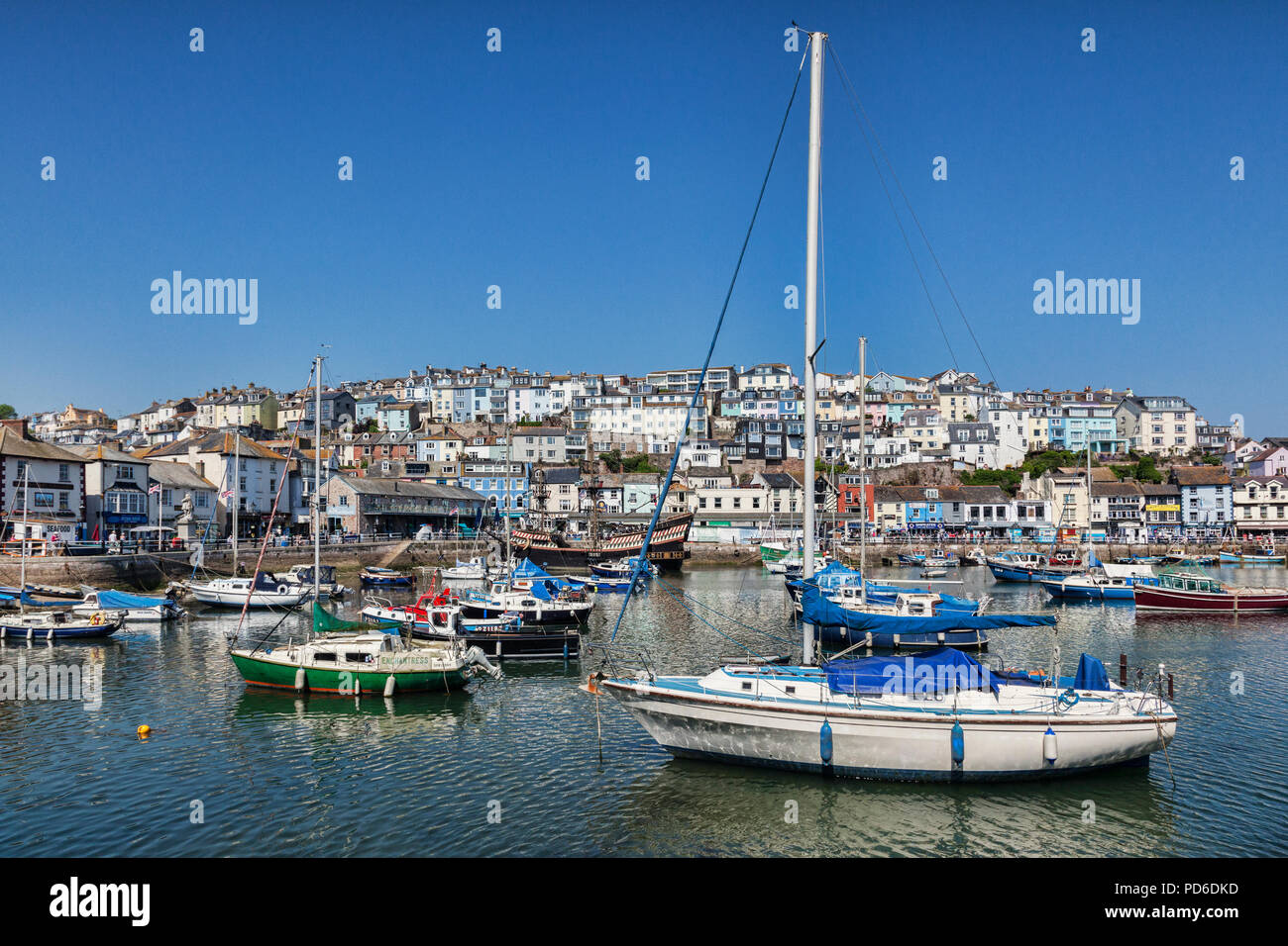23 May 2018: Brixham, Devon, UK - The harbour with the replica Golden Hind on a fine spring day with clear blue sky. - Stock Image