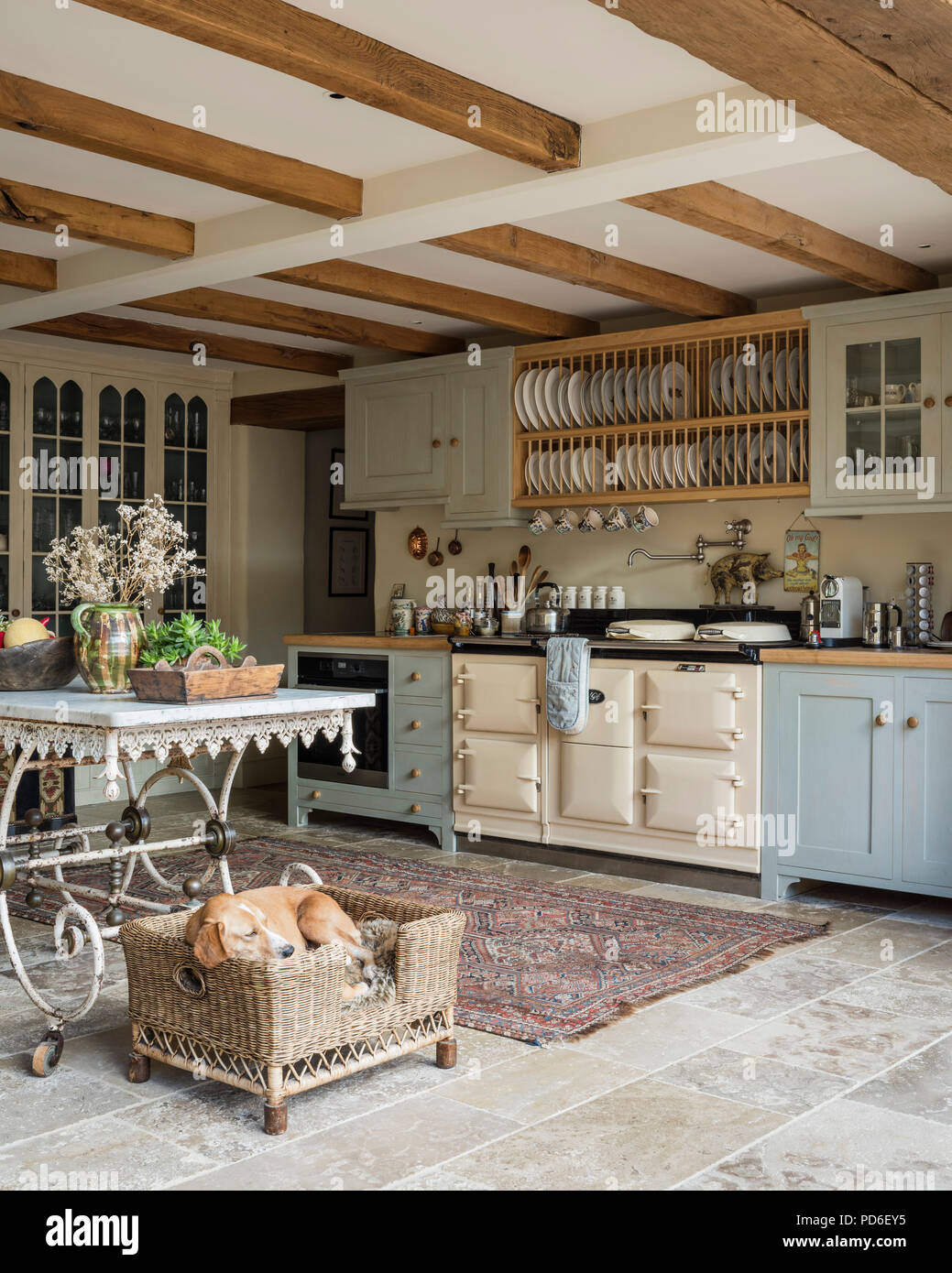 Light blue fitted farmhouse kitchen with plate rack and sleeping dog in basket. Stock Photo
