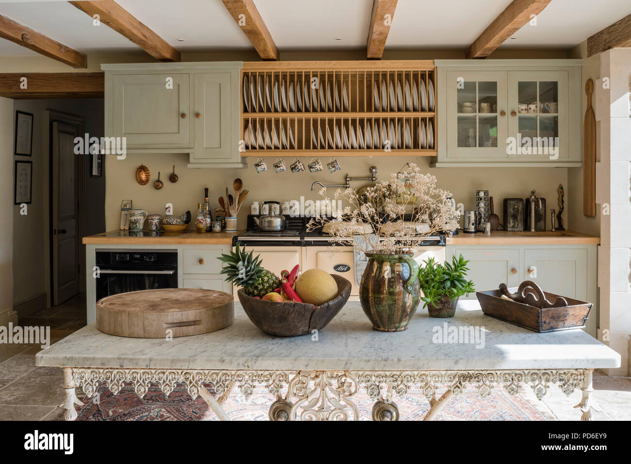 Wooden Plate Rack Above Aga In Green Fitted Farmhouse Kitchen Stock Photo Alamy
