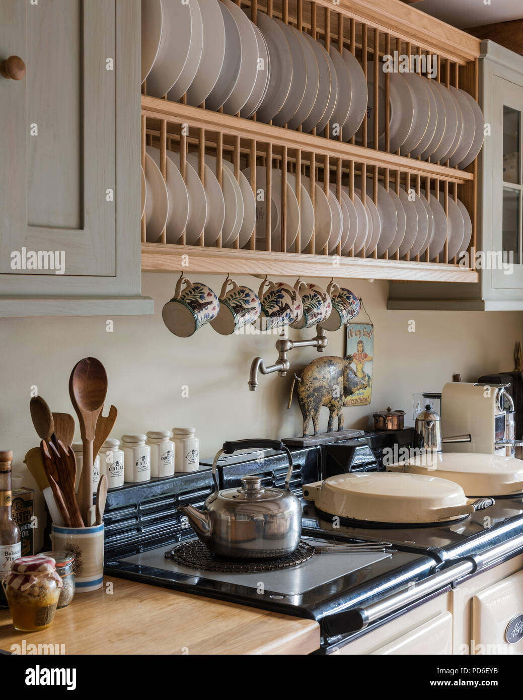 Wooden plate rack above AGA with kettle on hob - Stock Image
