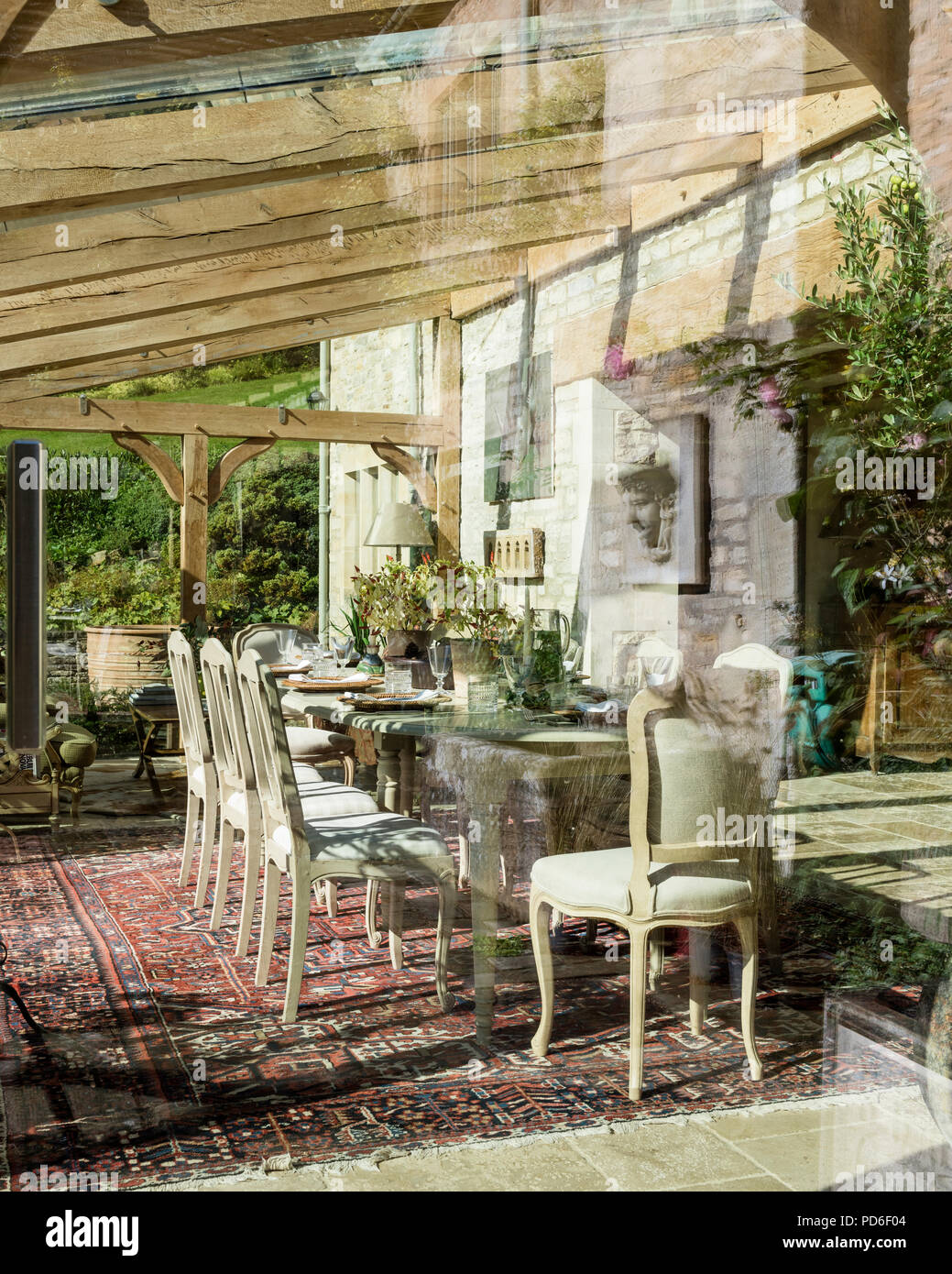 View into dining room of glass conservatory extension  19th century stone farmhouse. - Stock Image