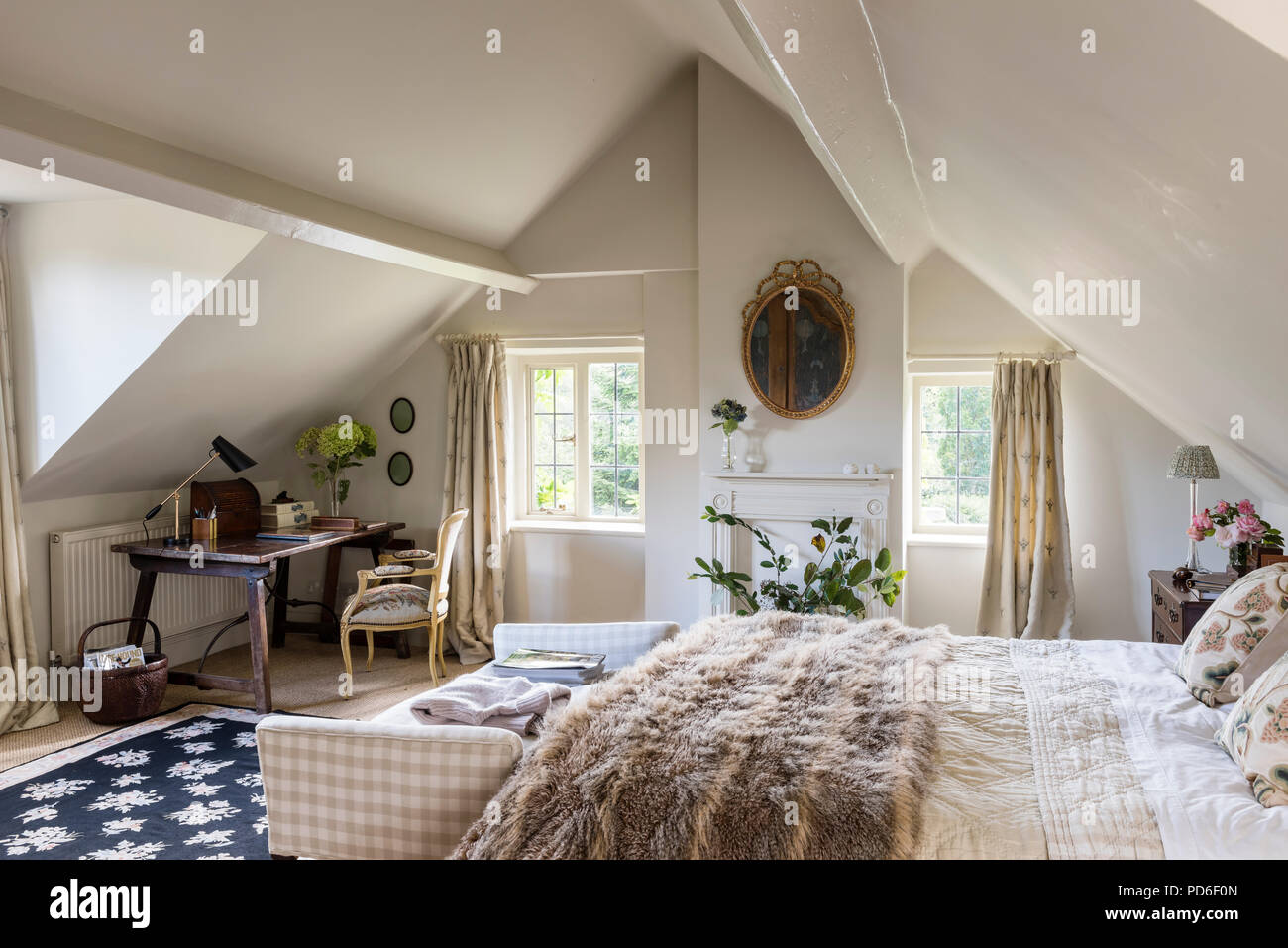 Desk and chair in attic with gilt framed artwork and double bed with fur throw Stock Photo