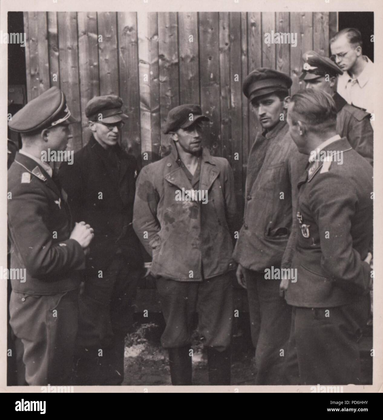 Image from the photo album of Oberleutnant Oscar Müller of  Kampfgeschwader 1: On 27th June 1941 Junkers Ju 88A-5 V4+ON (Werk. Nr. 4296) of 5./KG 1, was reported lost during a mission to Riga. Unteroffizier Friedrich Leibold (Air Gunner) was killed in action but the rest of the crew, Pilot Oberfeldwebel August Wiese (centre), Observer Feldwebel Martin Hasten (right) and Radio Operator Unteroffizier Armin Wuigk (with spectacles), returned in eight days. Here the crew are still disguised in civilian clothes and talking to Luftwaffe officers. - Stock Image