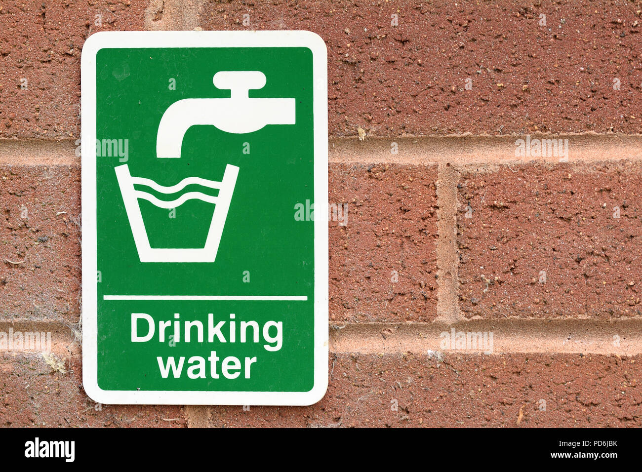 Drinking water sign with white text and tap faucet symbol and glass symbol on green background on red brick wall. Environmental water issues concept - Stock Image