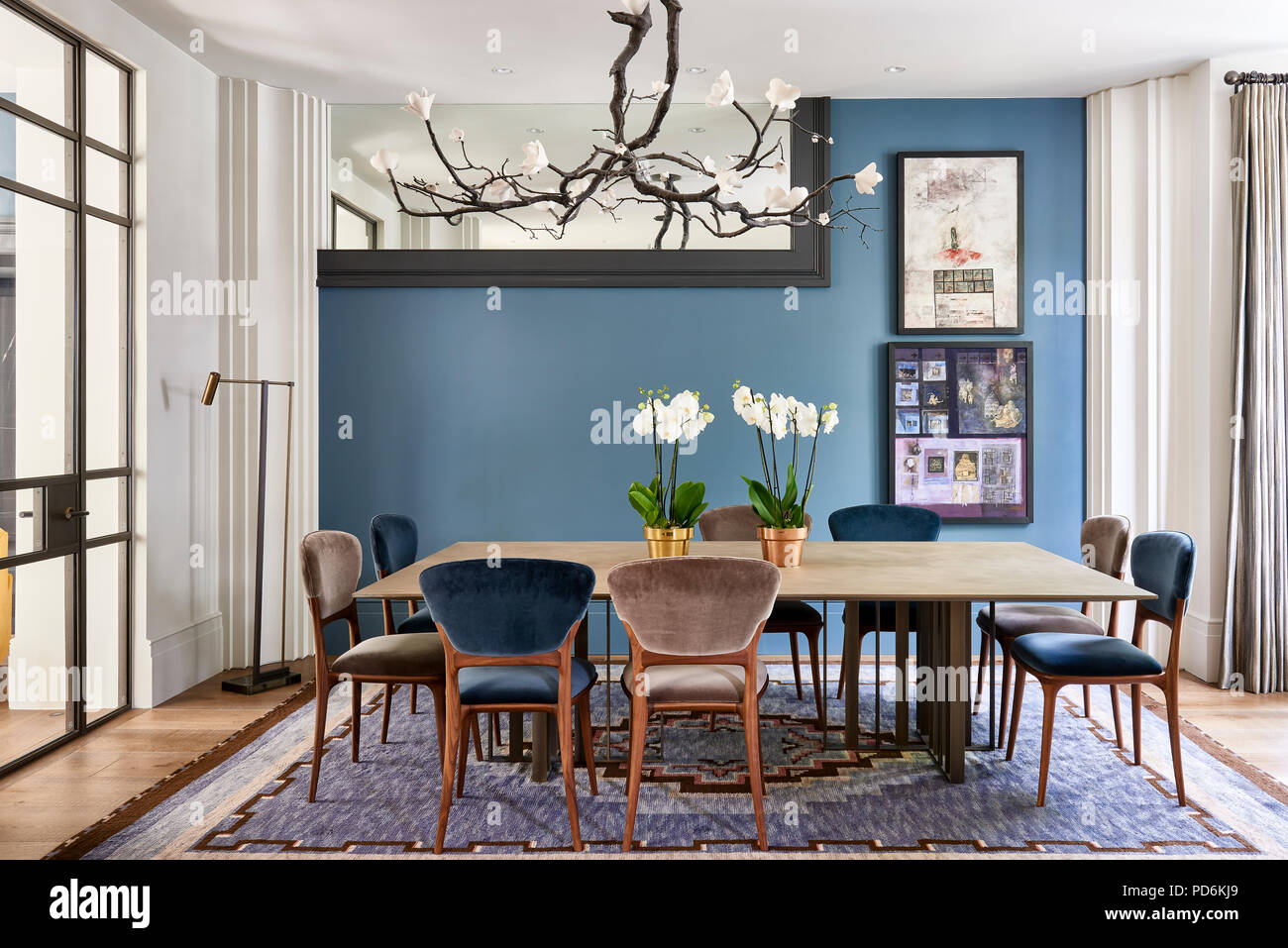 Magnolia Light Fitting Above Dining Table With Orchids And Part Of Mirror Frame Stock Photo Alamy