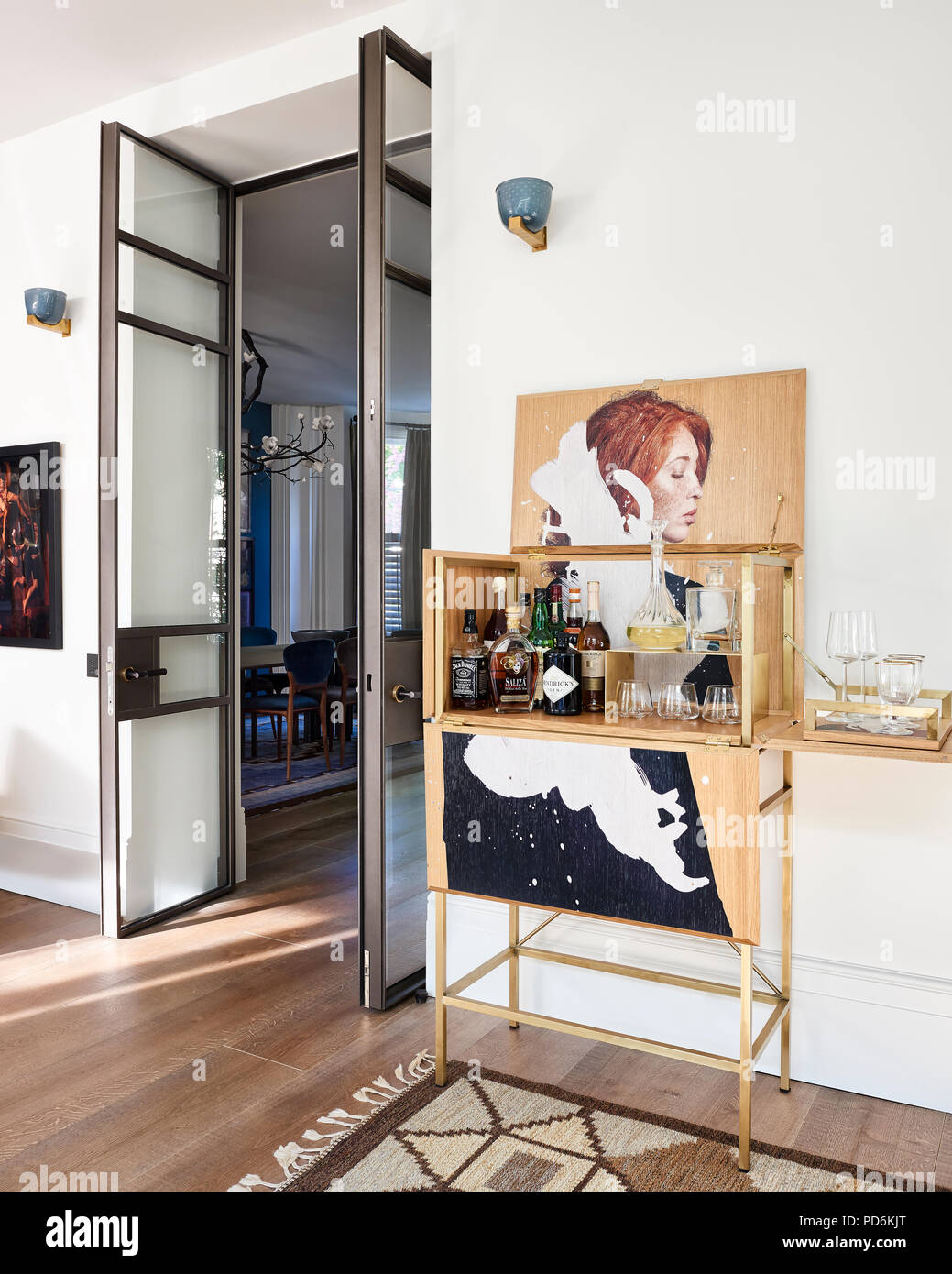 Drinks cabinet with artwork at double height doorway with blue and gold wall lights - Stock Image