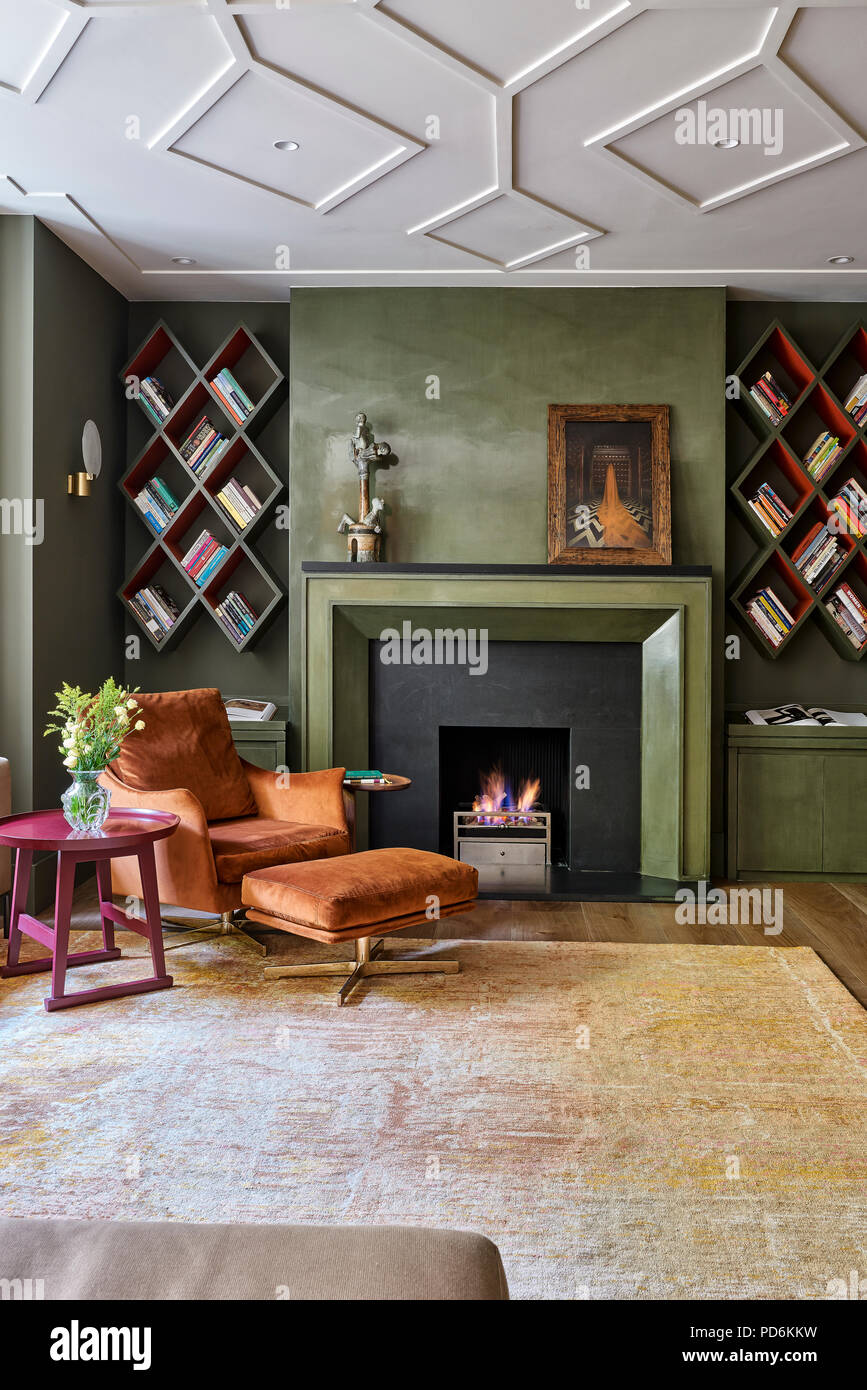 Vintage armchair and footstool withlit fire and wall mounted bookshelves - Stock Image