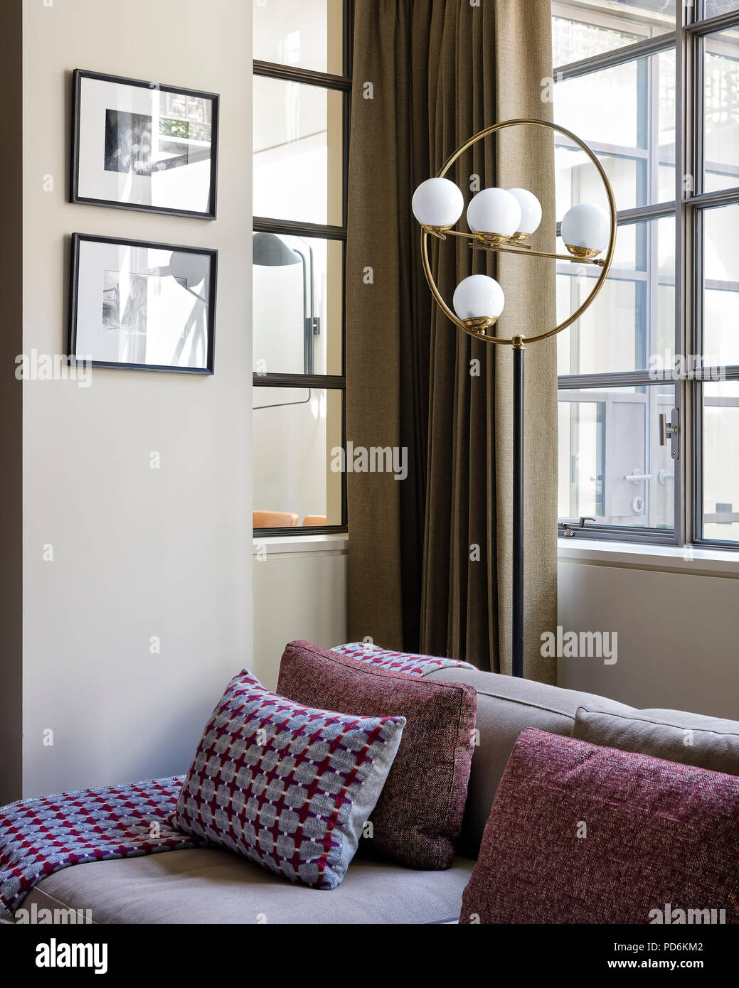 Vintage light fitting with framed artwork and sofa at window - Stock Image