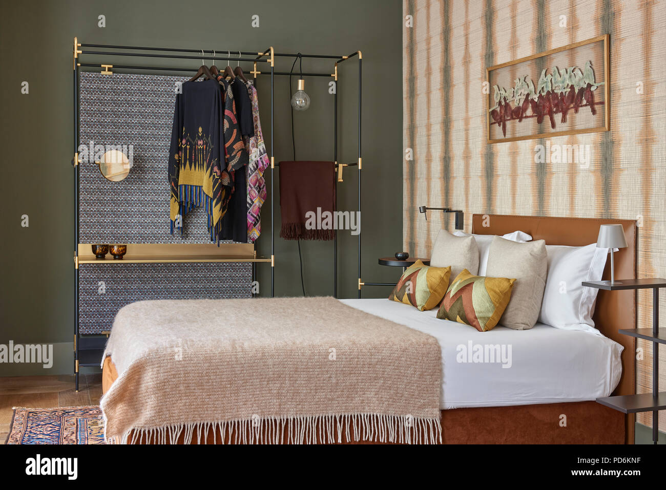 Ponchos hang on clothes rail by double bed with blaket. - Stock Image