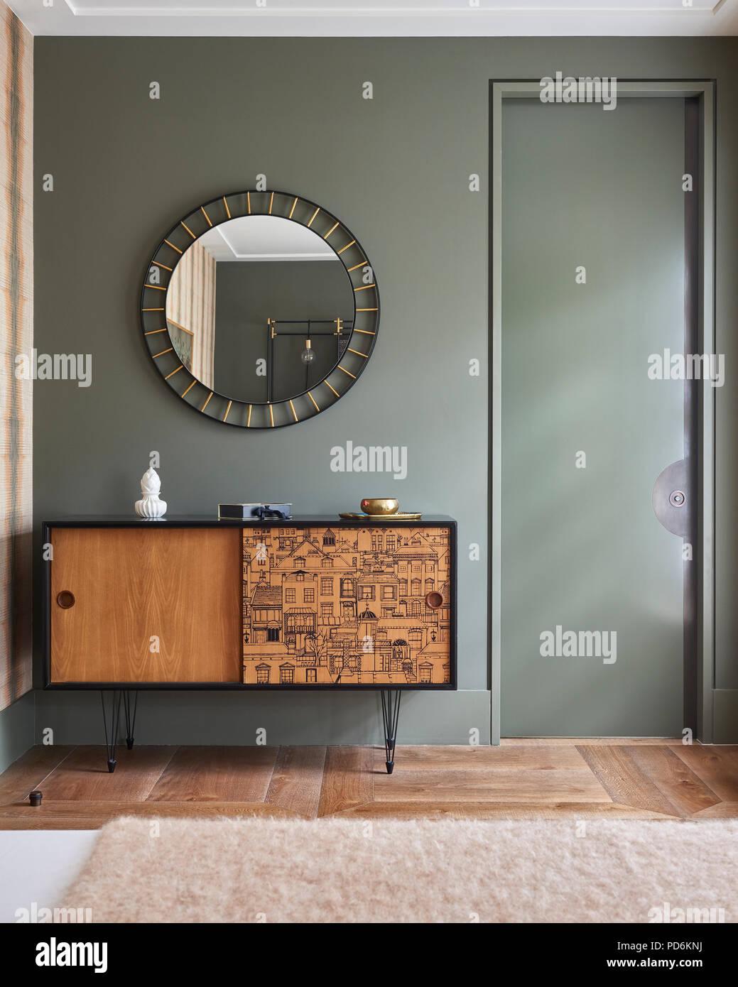 Circular mirror above retro sideboard. - Stock Image