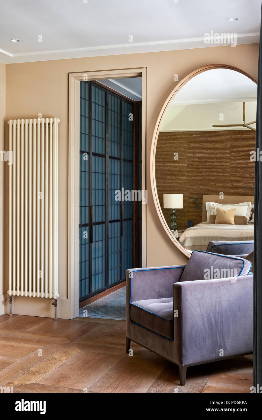 Oversized circular mirror and radiator with vintage chair at doorway. - Stock Image