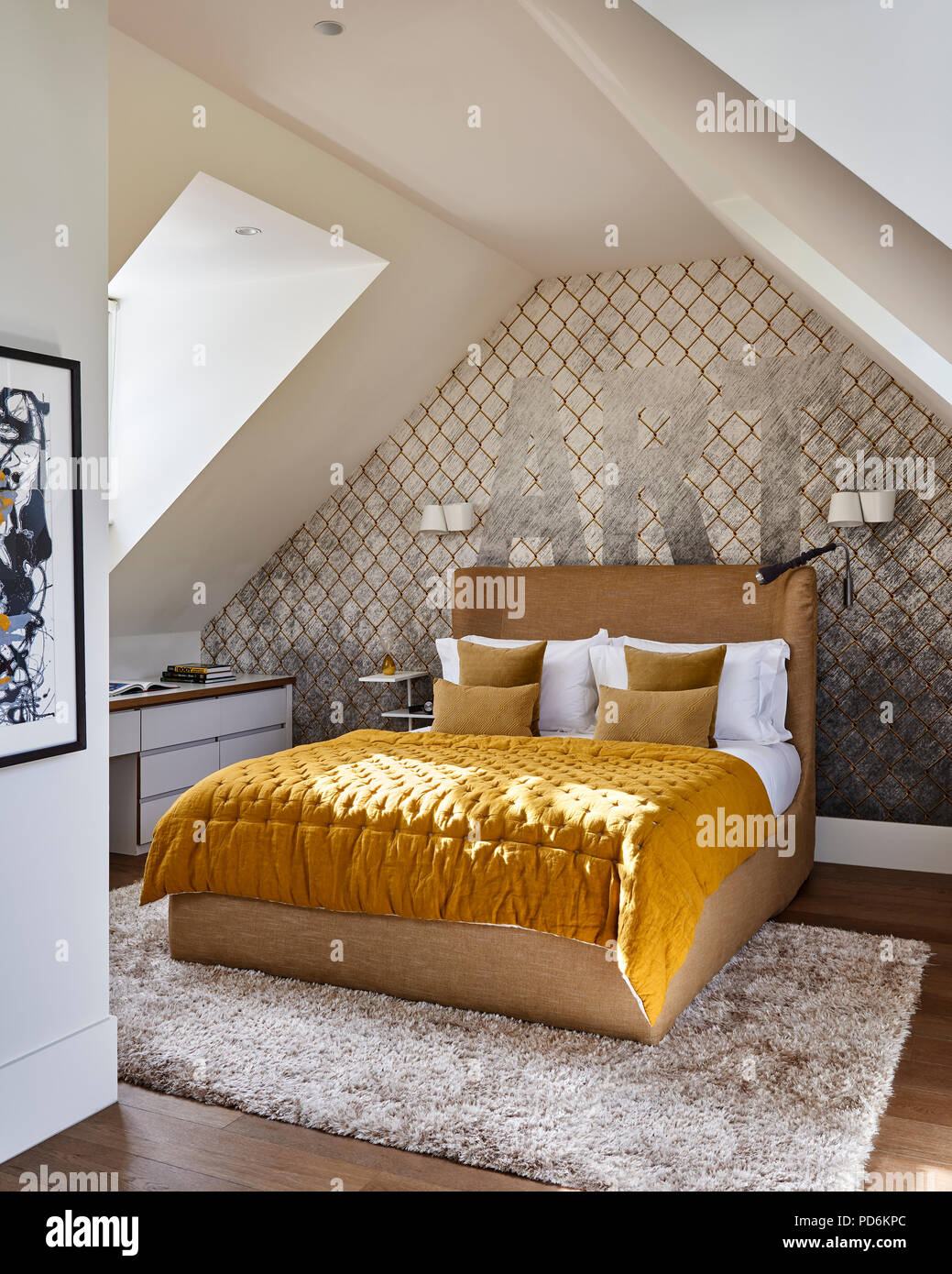 Yellow buttoned quilt on double bed below single word 'ART'. Stock Photo