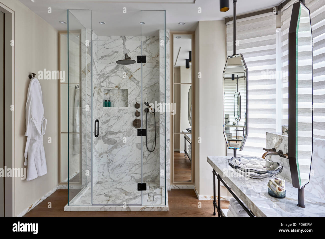 Bathrobe hangs with marble shower cubicle and lotus basin - Stock Image