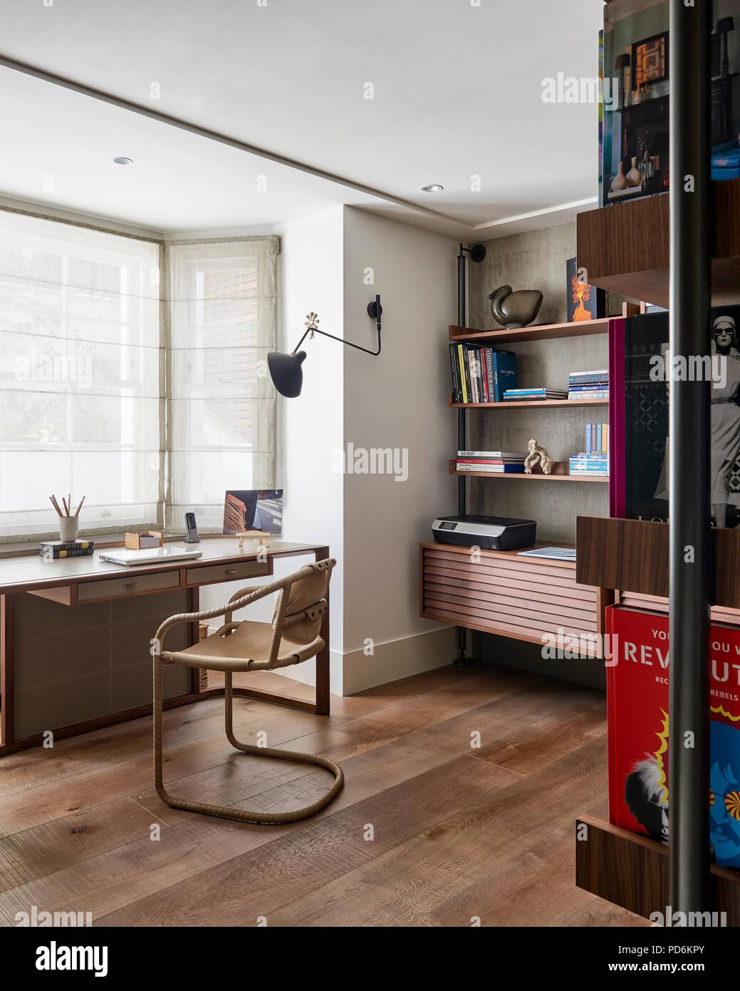 Deska nd chair in window with bookshelf - Stock Image